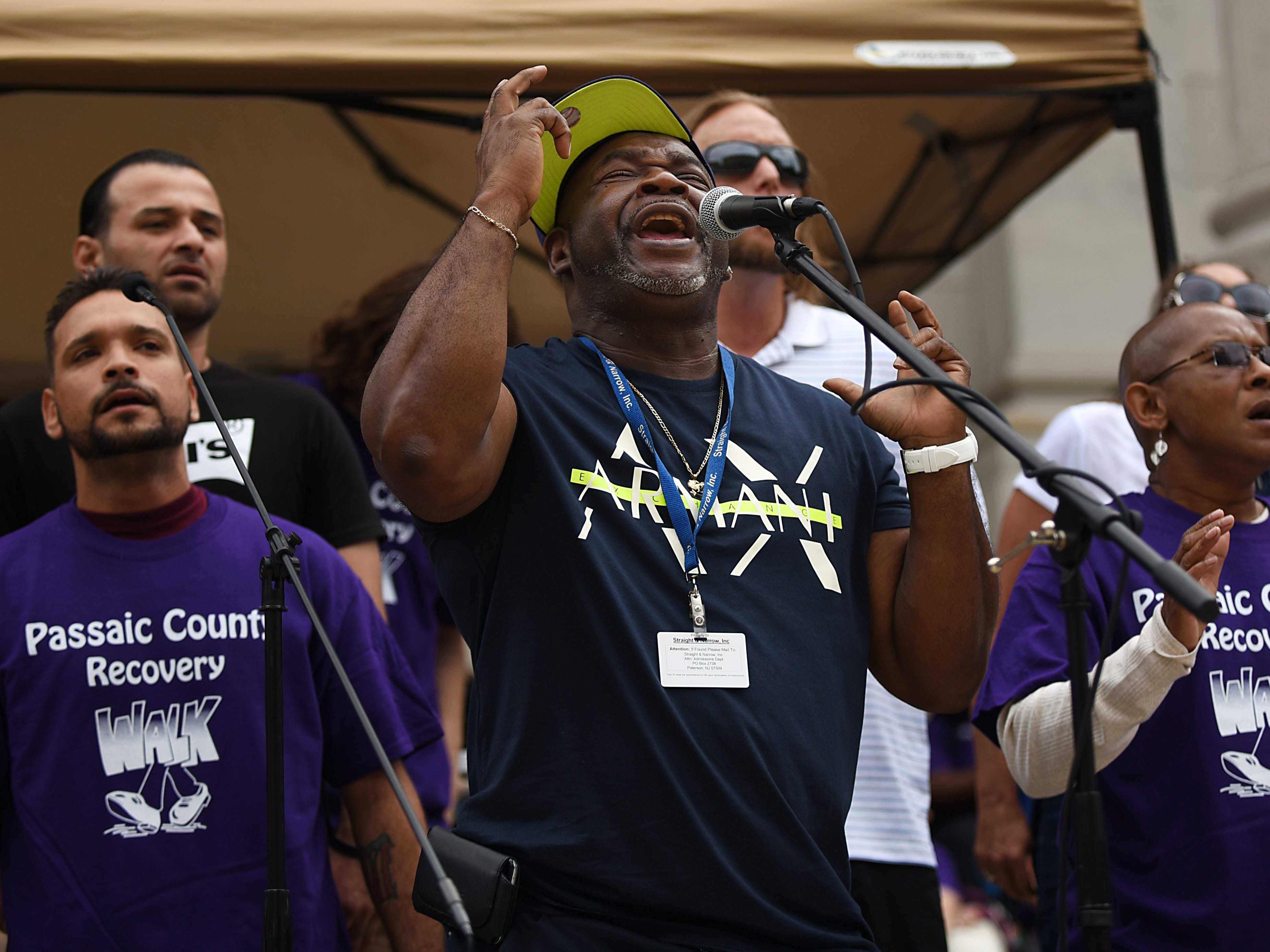 (Center) Irv DeBois, the Straight & Narrow Choir Liason, sings prior with the choir prior to the Passaic County Recovery Walk in Paterson on Saturday September 8, 2018.