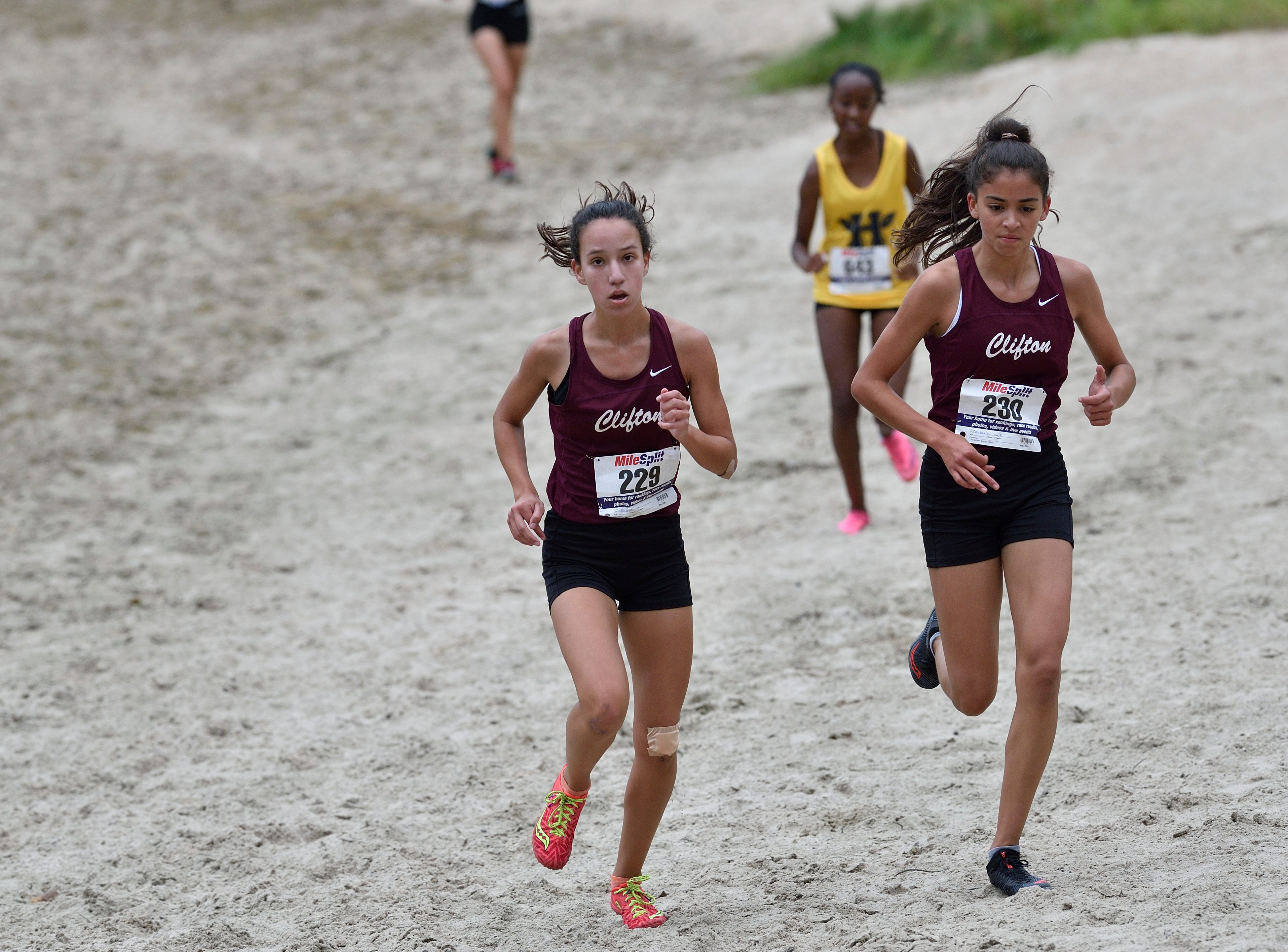 Mia Dubac (229) and Andrea Dubbels (230) of Clifton HS compete in the girls varsity A cross country race at Darlington County Park in Mahwah.