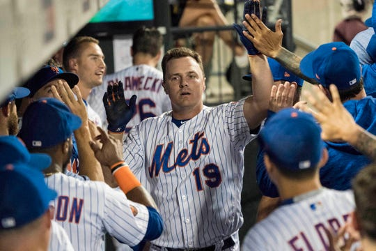 Teammates congratulate New York Mets right fielder Jay Bruce (19) in the dugout after he hit a home run during the second inning of the game at Citi Field.