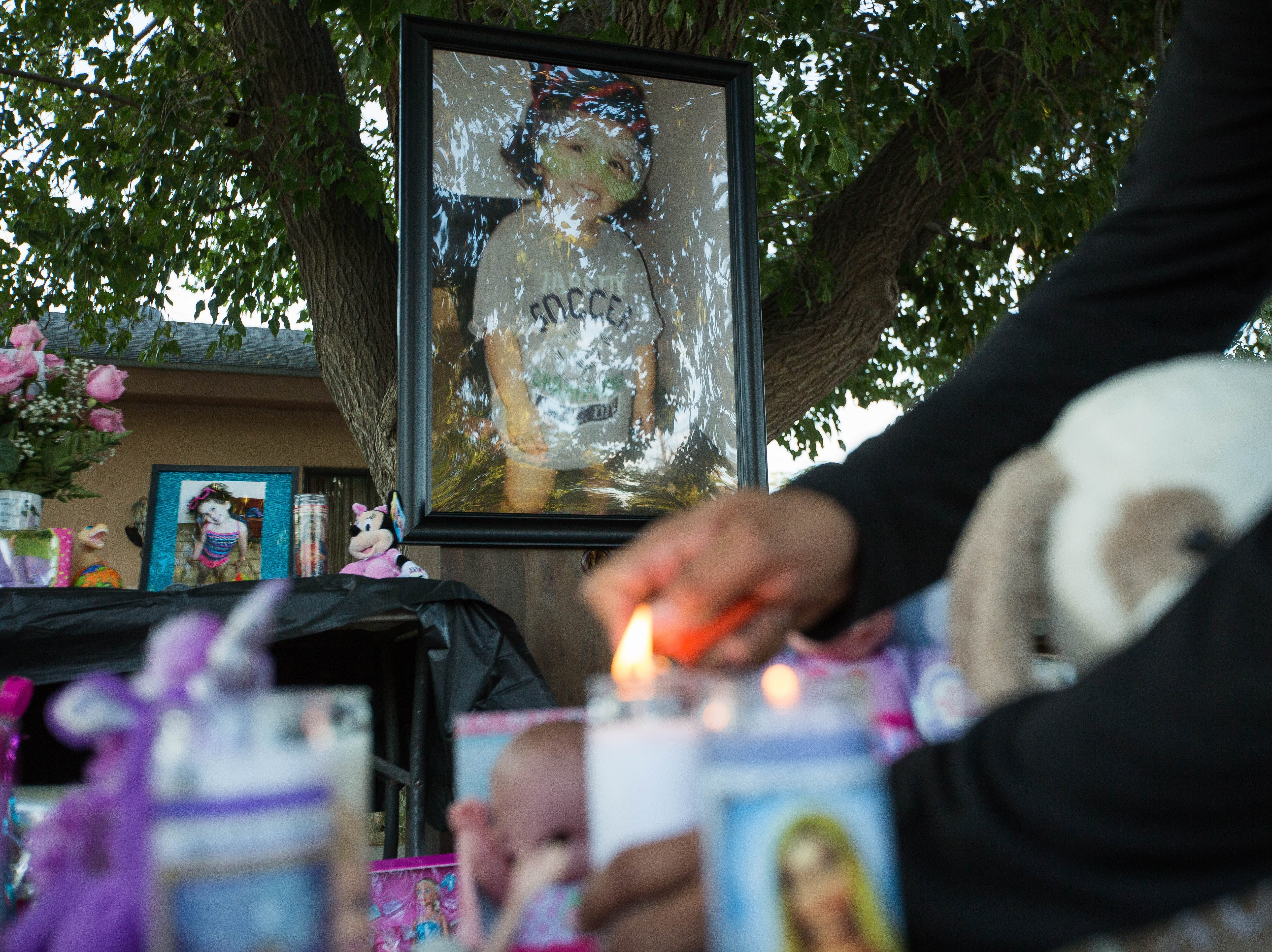 Frankie Duran, lights a candle on the memorial in front of photographs of Fabiola Rodriguez, 2,  who was found dead Thursday morning. Friends, Members of the Las Cruces Community and Family gathered outside of the house of Rodriguez's maternal grandparents for a candlelight vigil, Friday September 7, 2018.