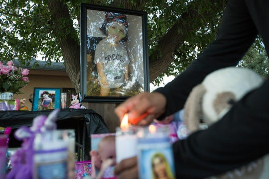 Frankie Duran lights a candle on the memorial in front of photographs of Fabiola Rodriguez, 2, who was found dead Thursday morning. Friends, members of the Las Cruces community and family gathered outside of the house of Rodriguez's maternal grandparents for a candlelight vigil, Friday September 7, 2018.