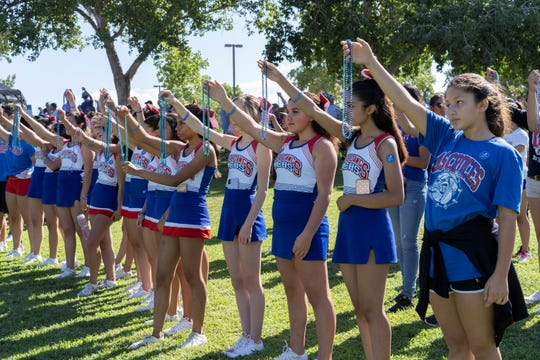 Las Cruces High School cheerleaders listen to speakers during the Out of the Darkness Community Walk for suicide prevention at Young Park Saturday. About 400 people showed up to the event hosted by the American Foundation for Suicide Prevention
