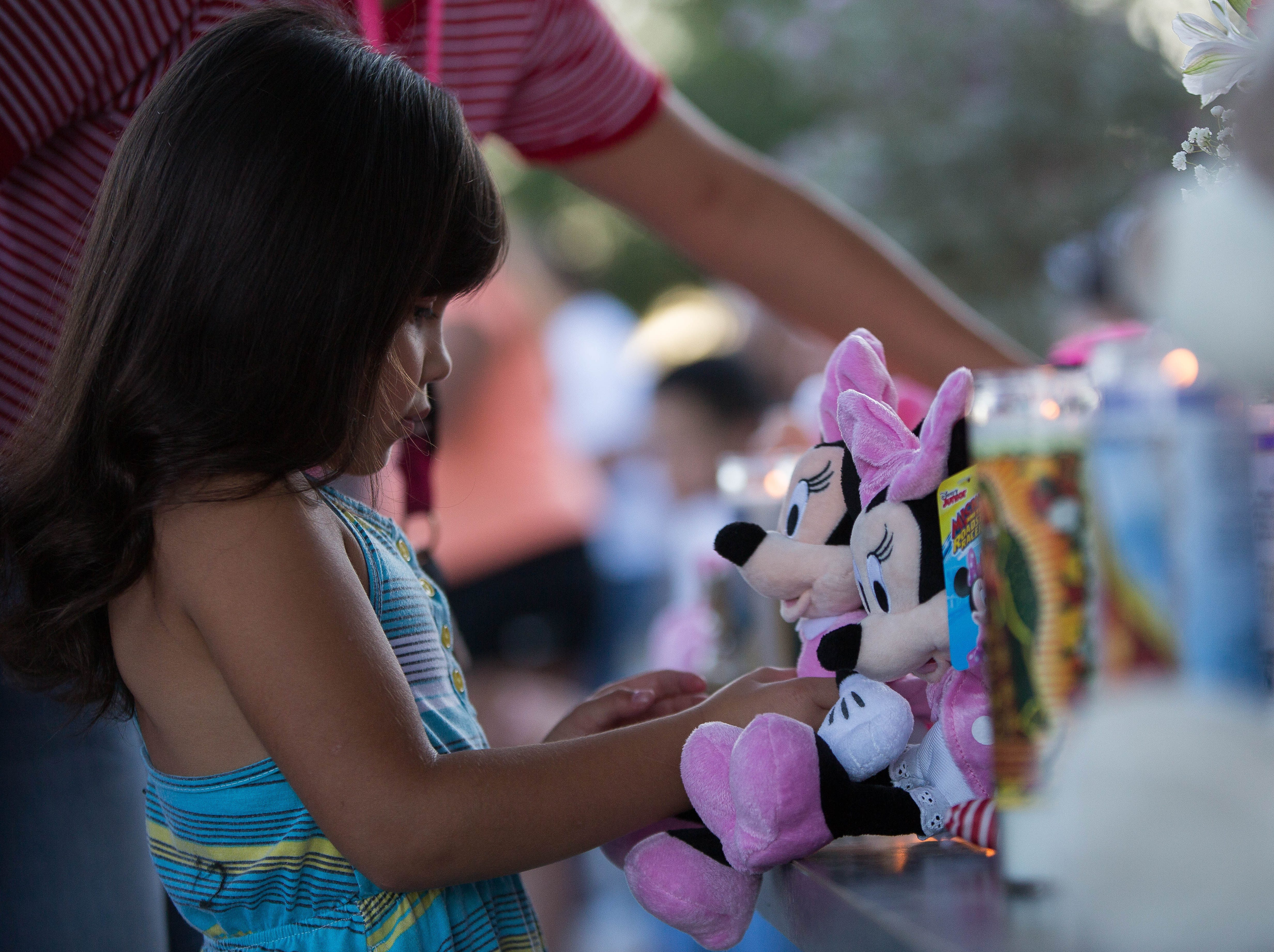 Jayley Meza, 5, lays a Minnie Mouse stuffed animal at the memorial for Fabiola Rodriguez, 2, Friday September 7, 2018 during a candlelight vigil for the two year old.