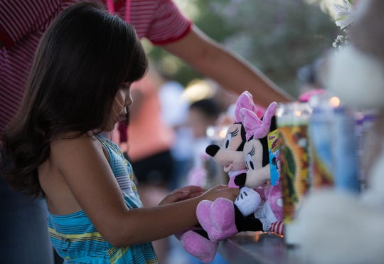 Jayley Meza, 5, lays a Minnie Mouse stuffed animal at the memorial for Fabiola Rodriguez, 2, Friday September 7, 2018 during a candlelight vigil for the 2-year-old.