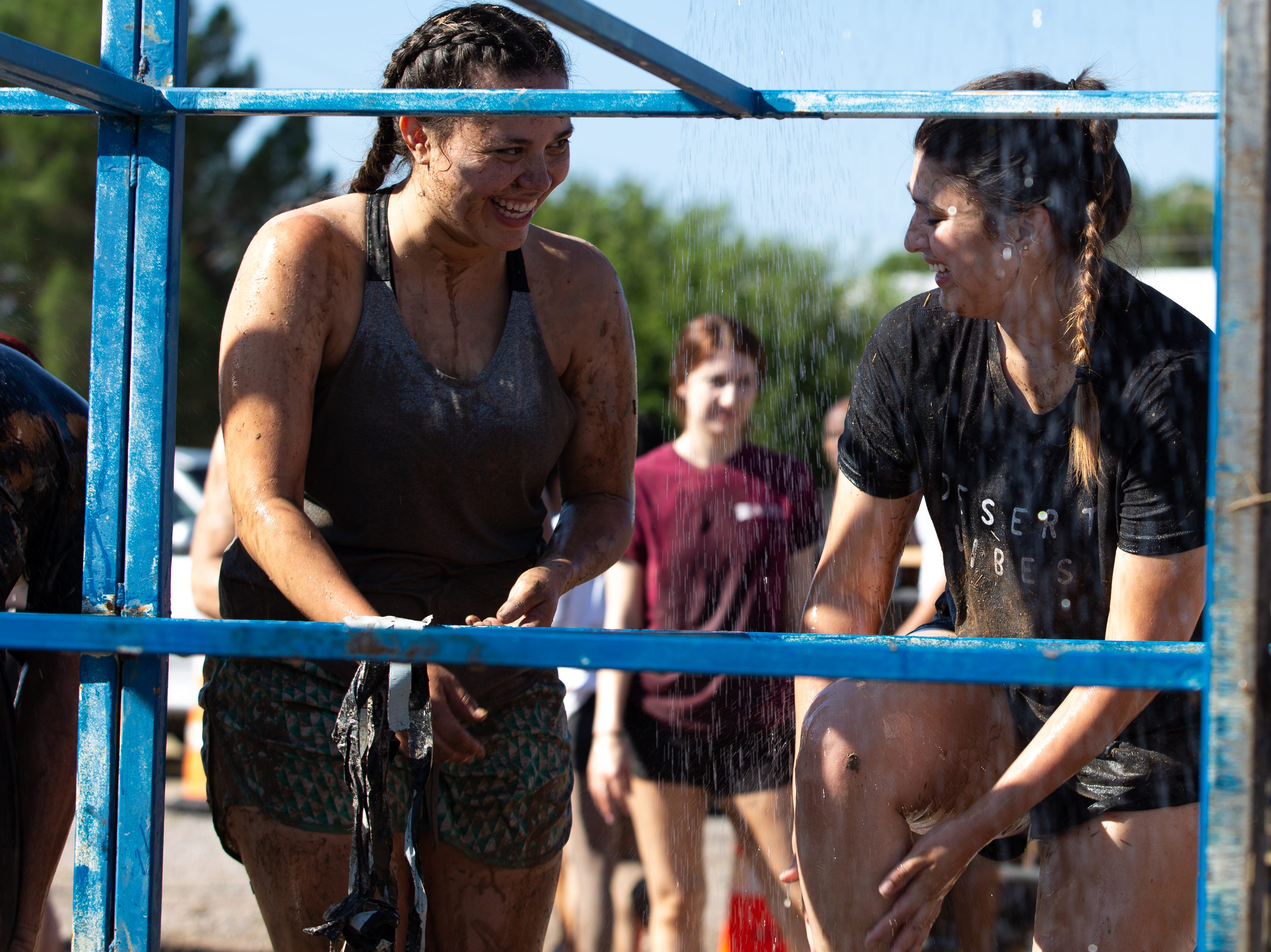 Vanessa Padilla, left and Julia Sierra having a good time washing off the mud at the 9th Annual Mudd Volleyball tournament on September 8, 2018.