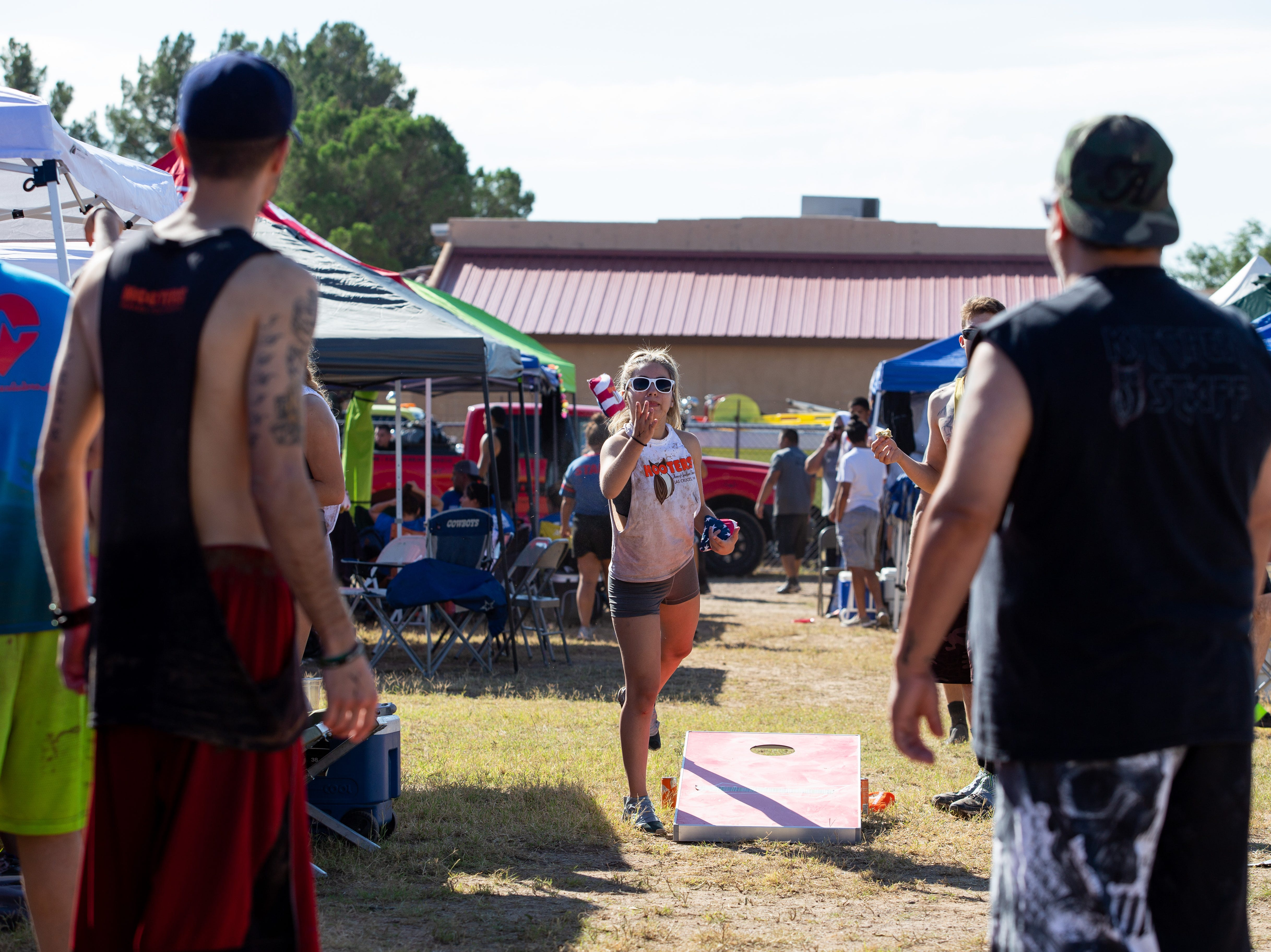 Danielle Silva of team Hooters flings a beanbag during a cornhole game at the 9th Annual Mudd Volleyball tournament on September 8, 2018.