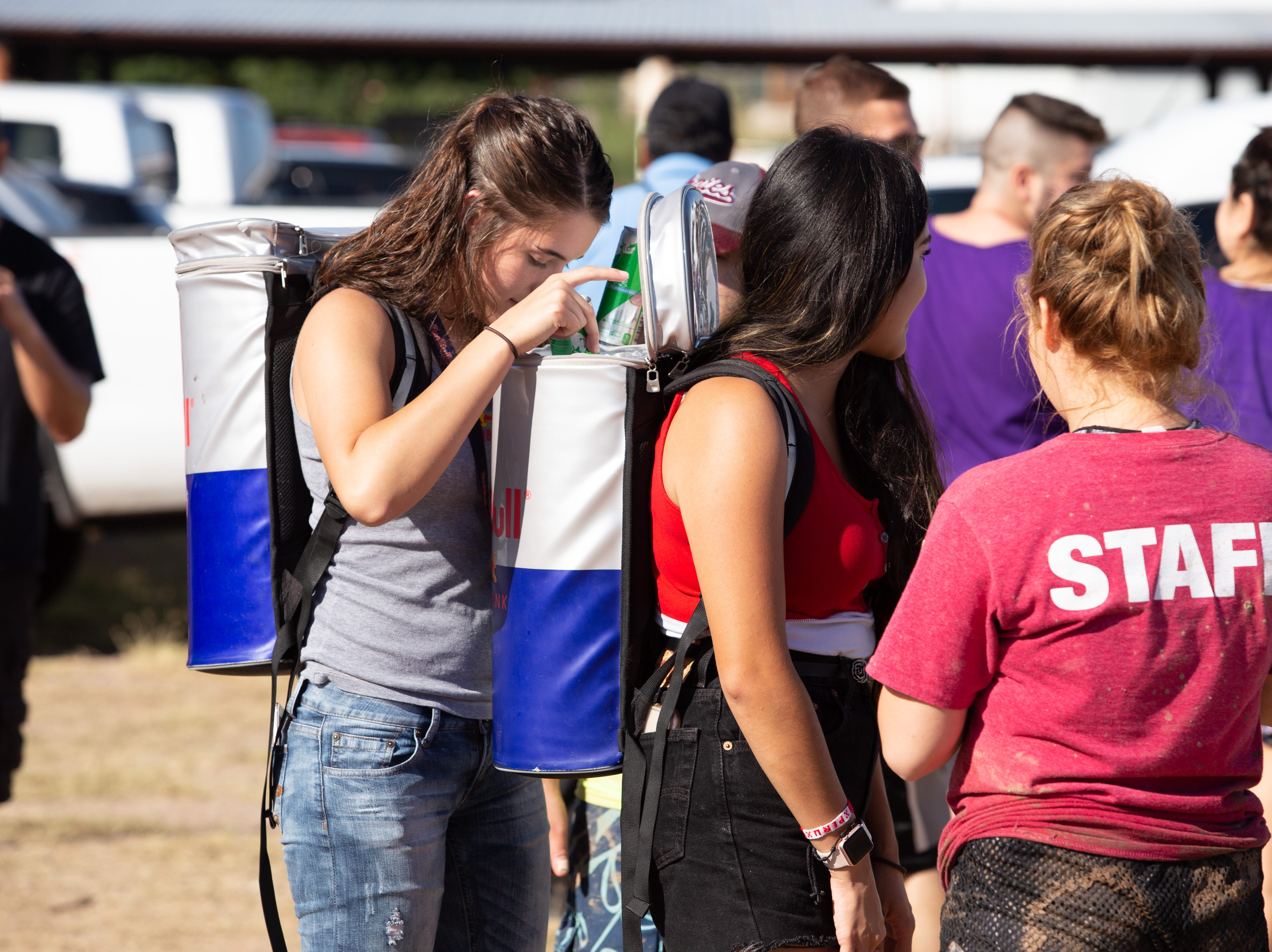 Red Bull Ladies Shaniah Lopez, left and Maryessa Chavez distribute complimentary energy drinks at the 9th Annual Mudd Volleyball tournament on September 8, 2018.