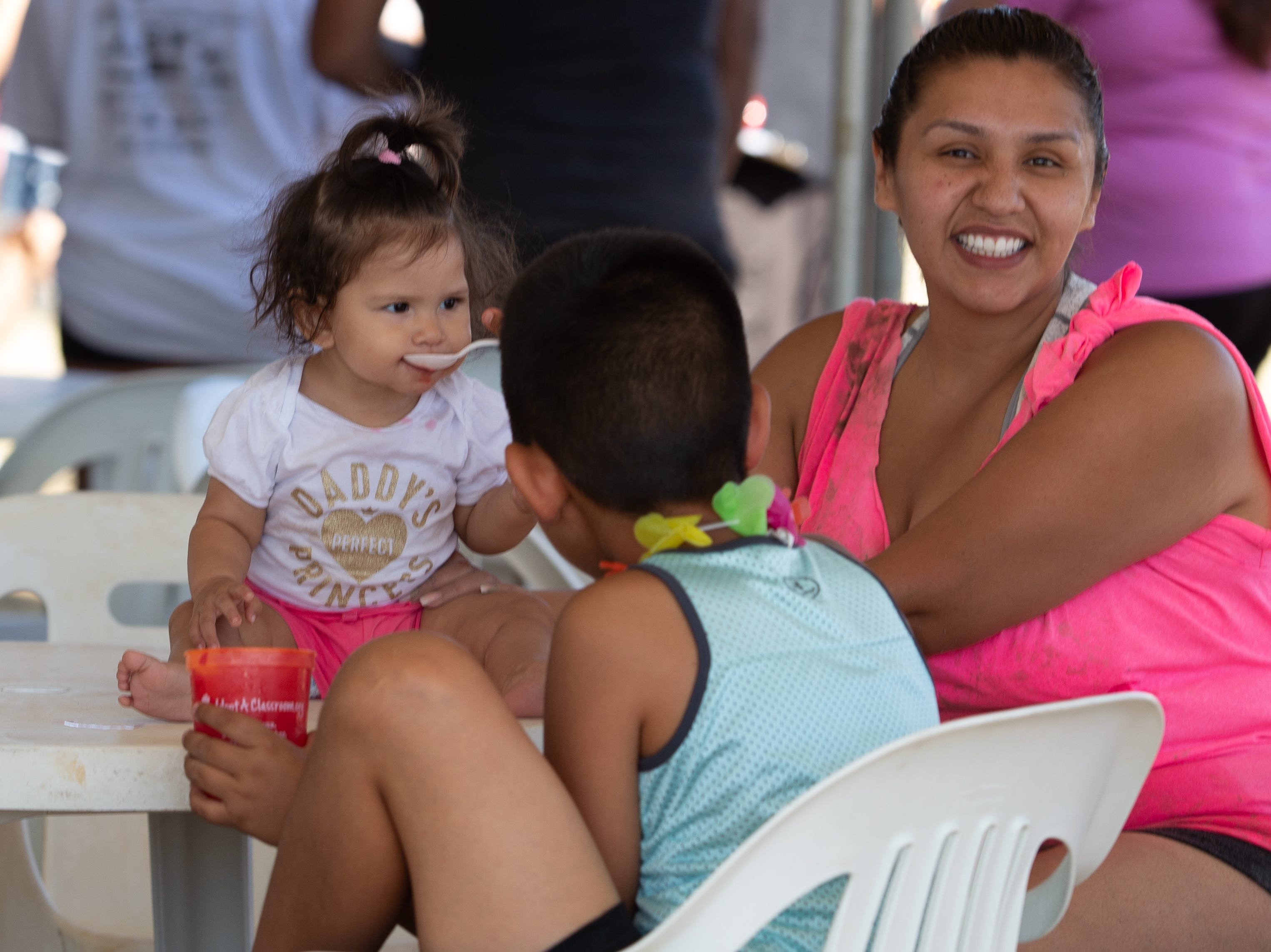 Vianny Moreno, 9 months enjoys a cool treat as her mother Viri looks on at the 9th Annual Mudd Volleyball tournament on September 8, 2018.