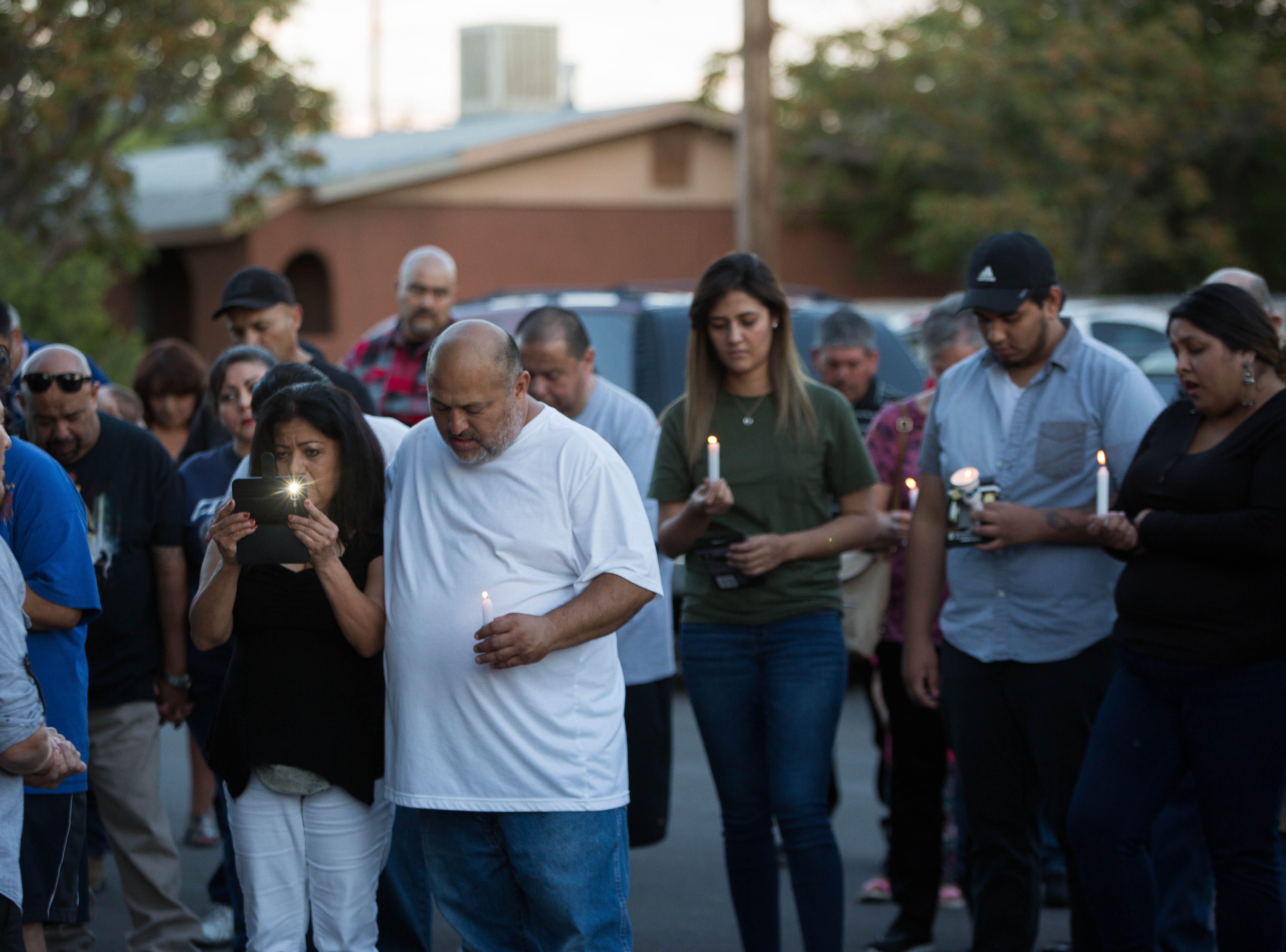 Joey Gonzales, center, grandfather of 2-year-old Fabiola Rodriguez, prays with the friends and family gathered for a candlelight vigil, Friday, September 7, 2018.