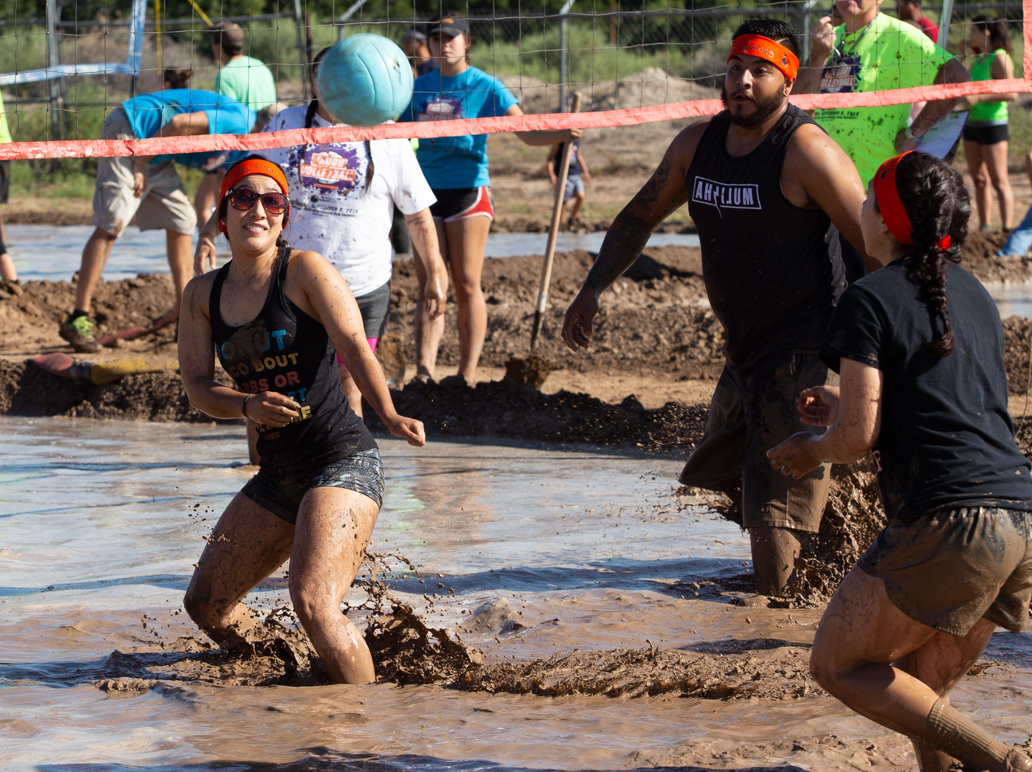 Volley Llamas team members race towards Jasmin Cisneros as she prepares to hit the ball during the 9th Annual Mudd Volleyball tournament on September 8, 2018.