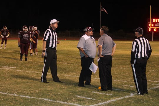 The Tularosa coaching staff discusses an official's call during the game against the Lordsburg Mavericks.