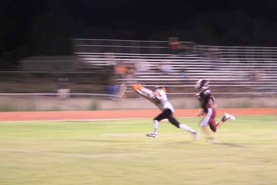 Lordsburg junior wide reciever #10 Josh Romero goes for a long pass but can't quite reach the ball.