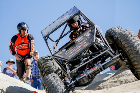 Jesse Haines, right, descends a rock crawl area with his unlimited with the help of his spotter, Troy Bailey Saturday during the W.E. Rock Grand Nationals at the Brown Spring Campground rock crawl in Glade Run north of Farmington.