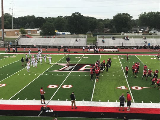 Players warm up on the brand new turf field before Friday night's game.
