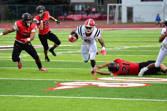 Westland John Glenn's Dante Barthwell (2) dashes up the field while Livonia Churchill's Mitchell Regan (21) tries to make a diving stop.