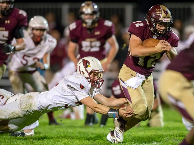 Omro's Jacob Kafer escapes a tackle by Mayville's Zach Weiss on Friday in Omro.