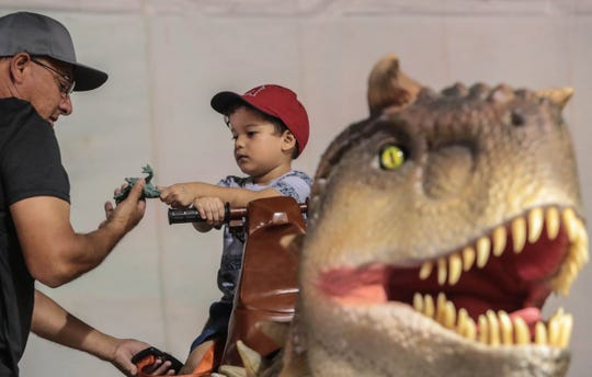 Three year old Aaron Gutierrez hands his toy dinosaur to his grandfather, Steven Gutierrez, of Coachella, as he rides a dinosaur at the Riverside County fairgrounds in Indio on Saturday, September 8, 2018.