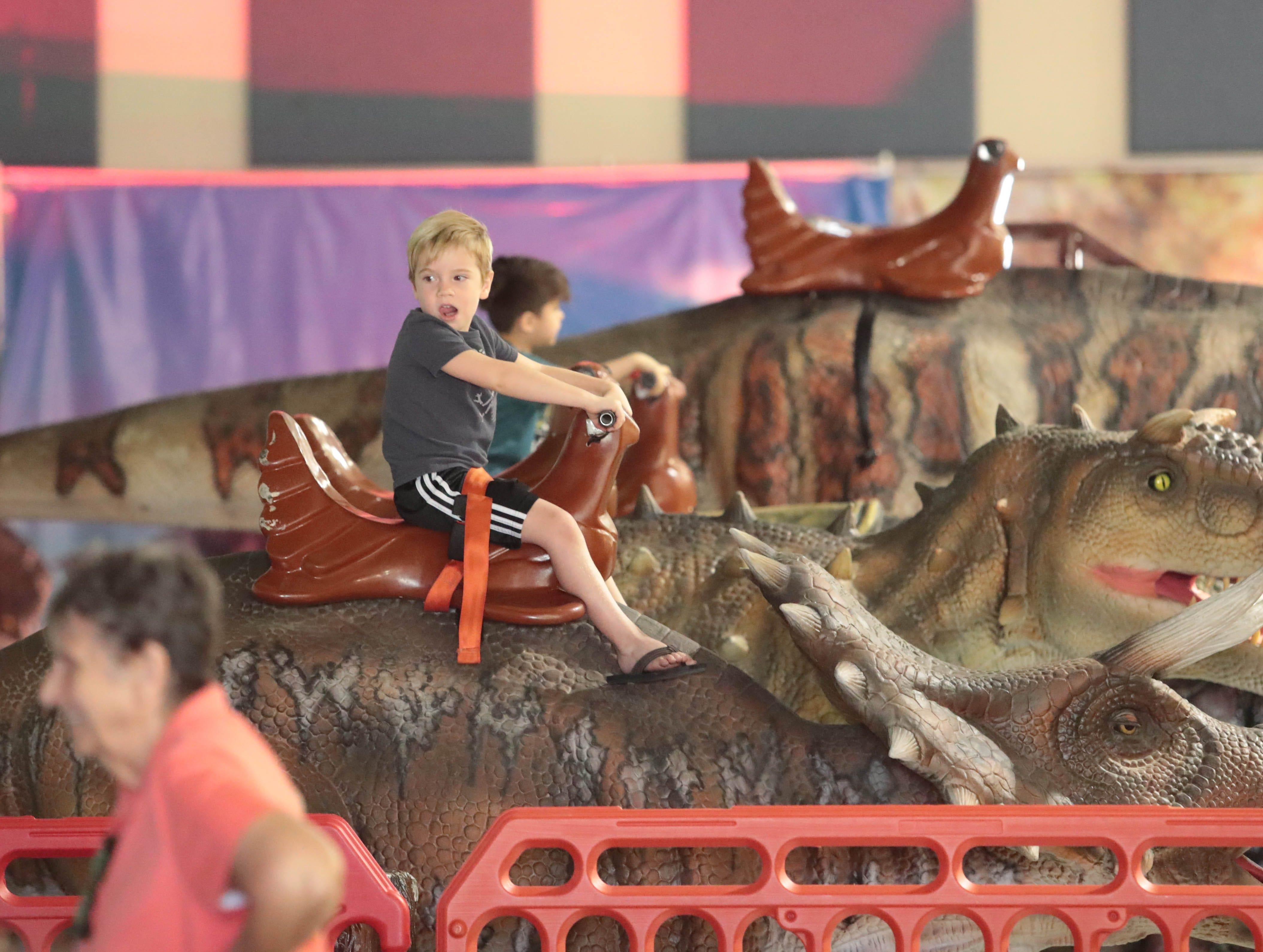Families enjoy the visiting dinosaur attraction, Jurassic Tours, at the Riverside County fairgrounds on Saturday, September 8, 2018 in Indio.