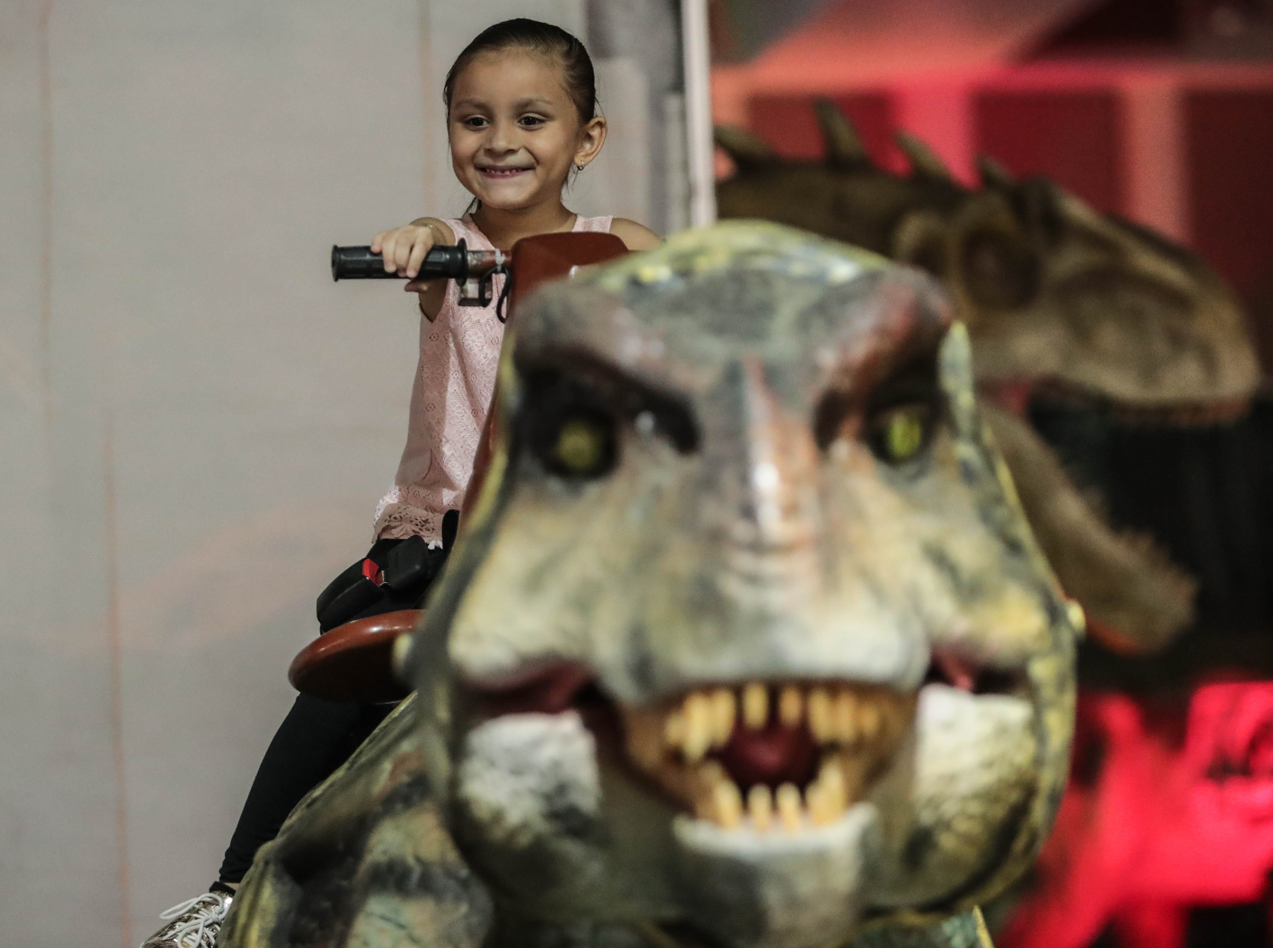 Jasmine Ruiz, 5, on a dinosaur at the visiting attraction, Jurassic Tours, at the Riverside County fairgrounds on Saturday, September 8, 2018 in Indio.