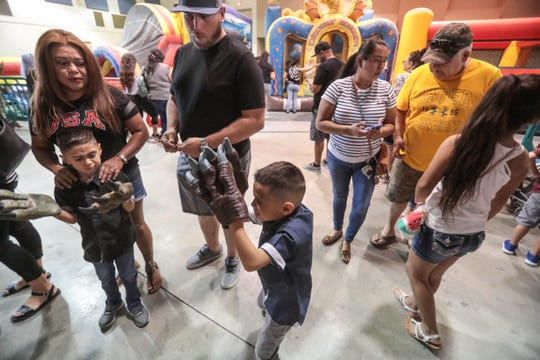 Twins Ryker Jonas and Reyaon Jonas, 5, play with their dinosaur claws while in a line at the Jurassic Tours event a the Riverside County fairgrounds on Saturday, September 8, 2018 in Indio.