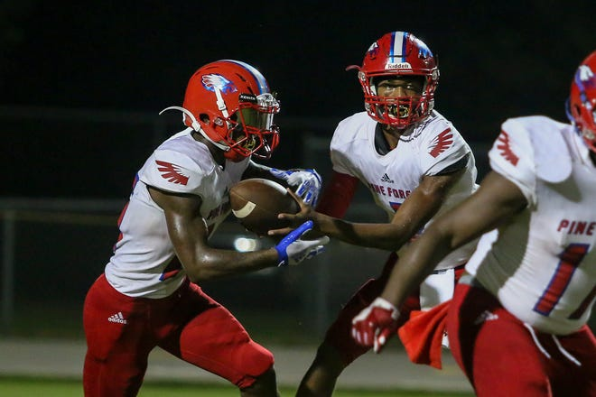 Pine Forest quarterback Ladarius Clardy (2) hands the ball off to Anwar Lewis (25) against the Patriots at Pace High School on Friday, September 7, 2018.