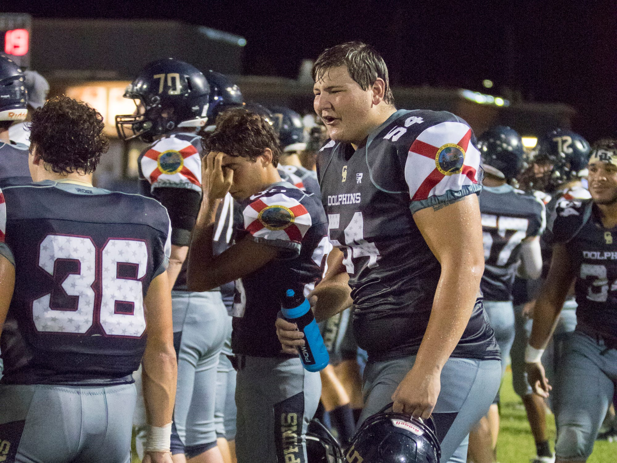 Joseph Stone (54) talks with teammates on the sideline during the Tate vs Gulf Breeze football game at Gulf Breeze High School in Pace on Friday, August 31, 2018.