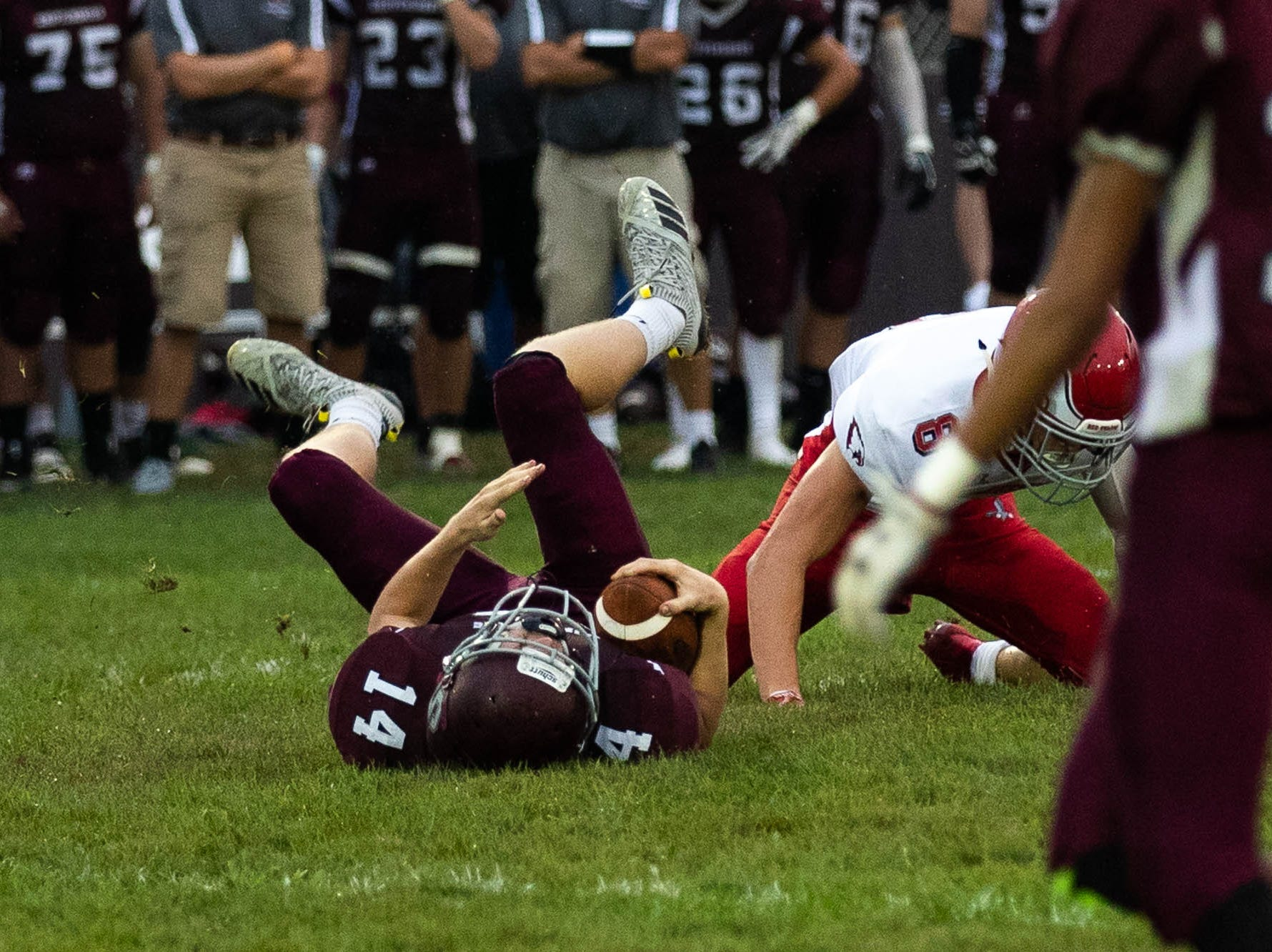 Shippensburg's Andrew Hoch (14) rolls through the field after being tackled by Bermudian Springs' Chase McMillan (8) during a football game between Shippensburg and Bermudian Springs, Friday, Sept. 7, 2018, at Shippensburg High School.