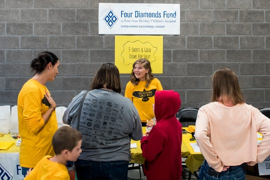 "Hanover High School senior Saige Stevens, center, runs a table during Hanover's ""Gold-Out"" event to raise raise money and awareness for pediatric cancer on September 7, 2018."