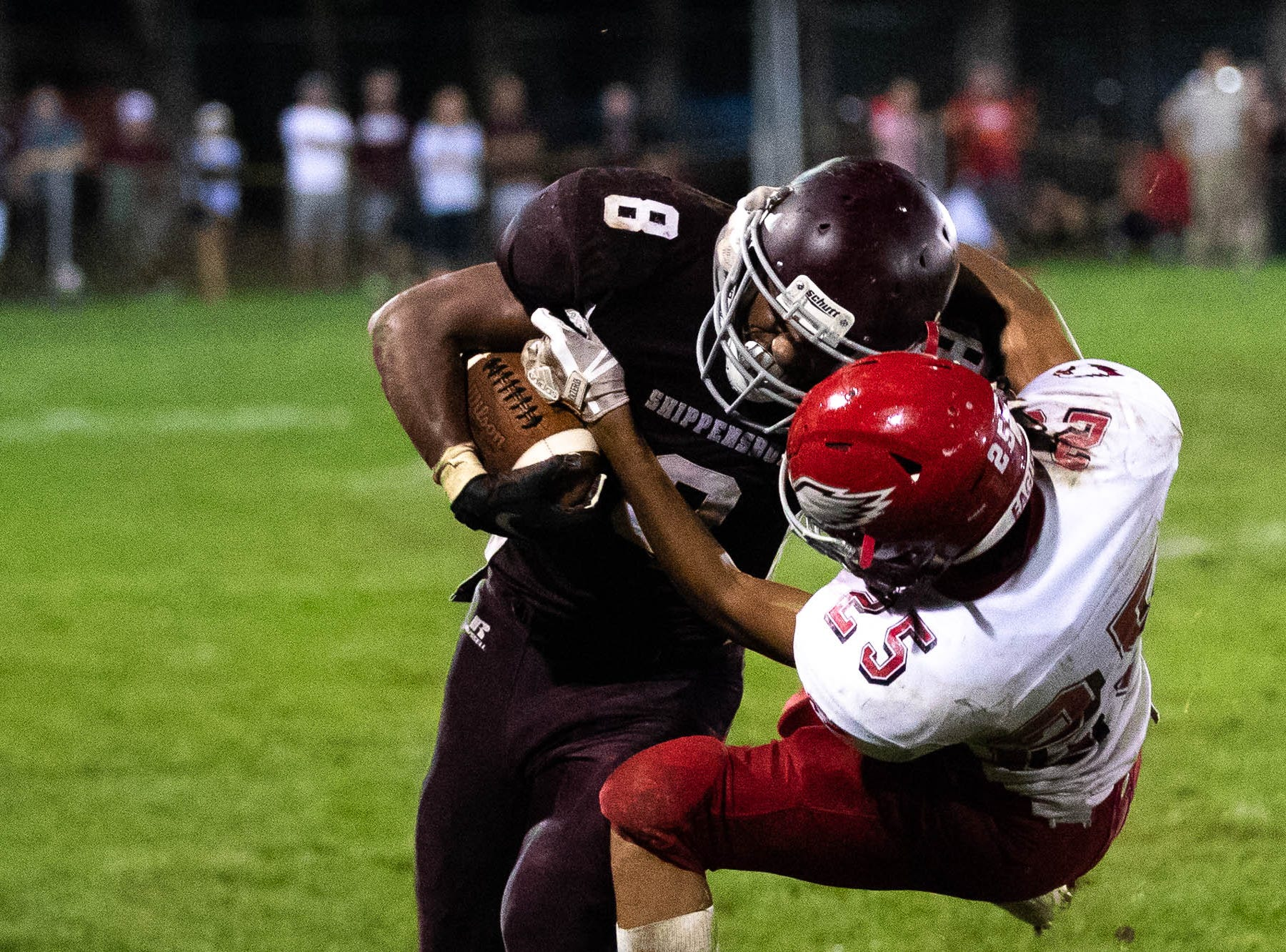 Shippensburg's Adam Houser (8) is taken down by Bermudian Springs' JJ Talley (25) during a football game between Shippensburg and Bermudian Springs, Friday, Sept. 7, 2018, at Shippensburg High School. The Shippensburg Greyhounds defeated the Bermudian Springs Eagles 31-17.