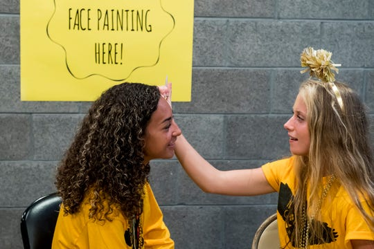 """Ella Krenzer, right, paints the face of Tianna Gray during Hanover High School's """"Gold-Out"""" event to raise raise money and awareness for pediatric cancer prior to their football game on September 7, 2018."""