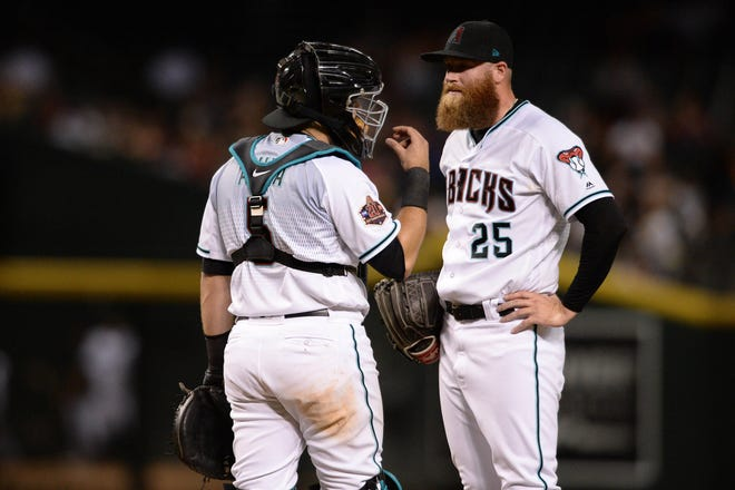 Sep 7, 2018; Phoenix, AZ, USA; Arizona Diamondbacks relief pitcher Archie Bradley (right) and catcher Alex Avila (5) meet at the mound during the eighth inning against the Atlanta Braves at Chase Field.