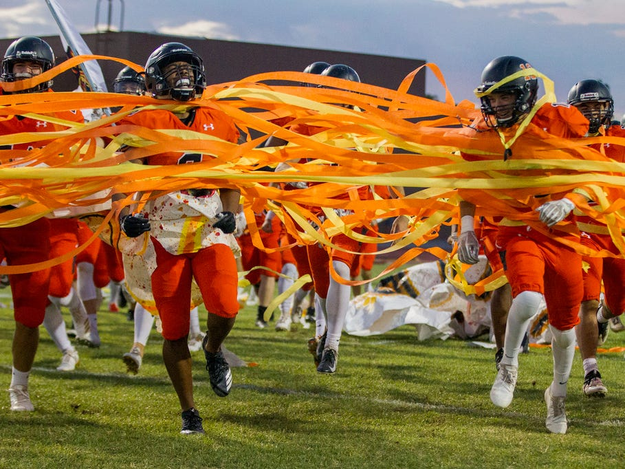 Corona del Sol players run through banners before their game with Boulder Creek in Tempe Friday, Sept. 7, 2018. #azhsfb