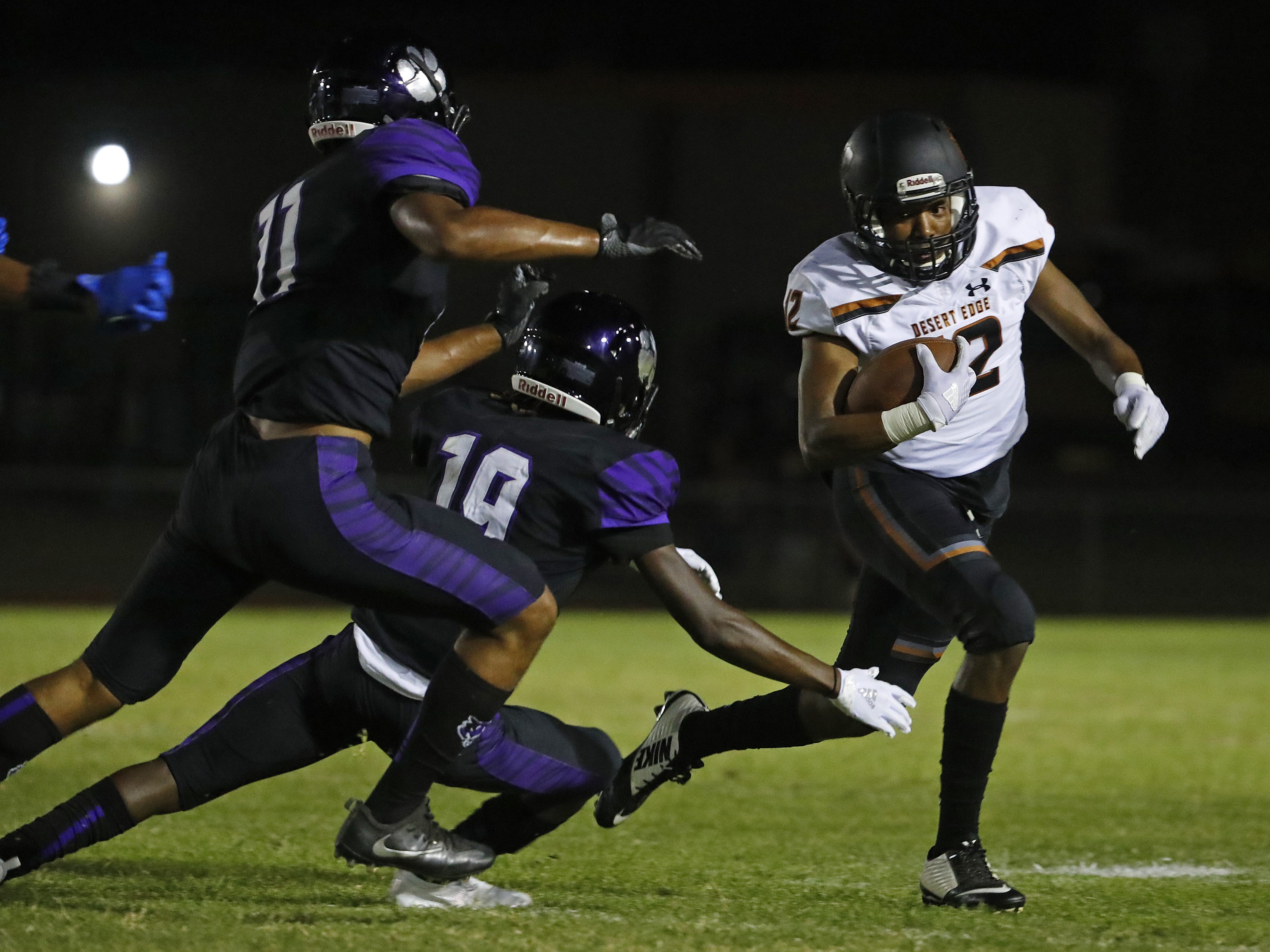 Desert Edge's Kennith Powell (12) breaks tackles from Millennium's Daylon Storey (11) and Kaysan Barnett (19) during a game at Millennium High School in Goodyear, Ariz. on Sept. 7, 2018.