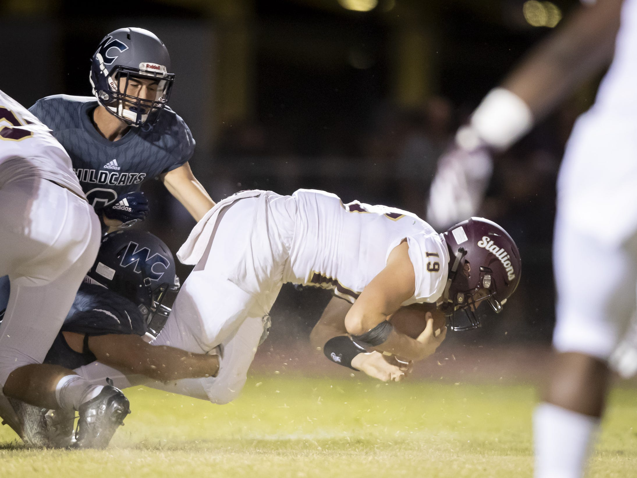 Junior quarterback Kaiden Lansford (19) of the Shadow Ridge Stallions is tackled by senior defensive tackle Jason Hickson (56) of the Willow Canyon Wildcats at Willow Canyon High School on Friday, September 7, 2018 in Surprise, Arizona. #azhsfb