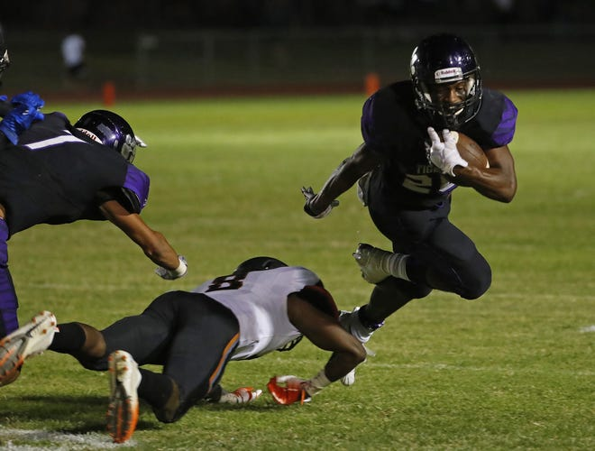 Millennium's Isaac Oliver (26) tries to jump a tackle from Desert Edge's Anthony Davis during a game at Millennium High School in Goodyear, Ariz. on Sept. 7, 2018.