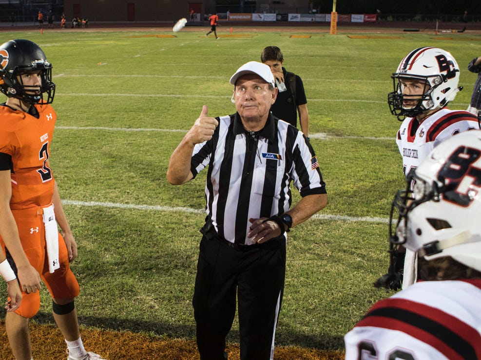 An AIA referee flips the coin between Corona del Sol and   Boulder Creek before their game in Tempe Friday, Sept. 7, 2018. #azhsfb