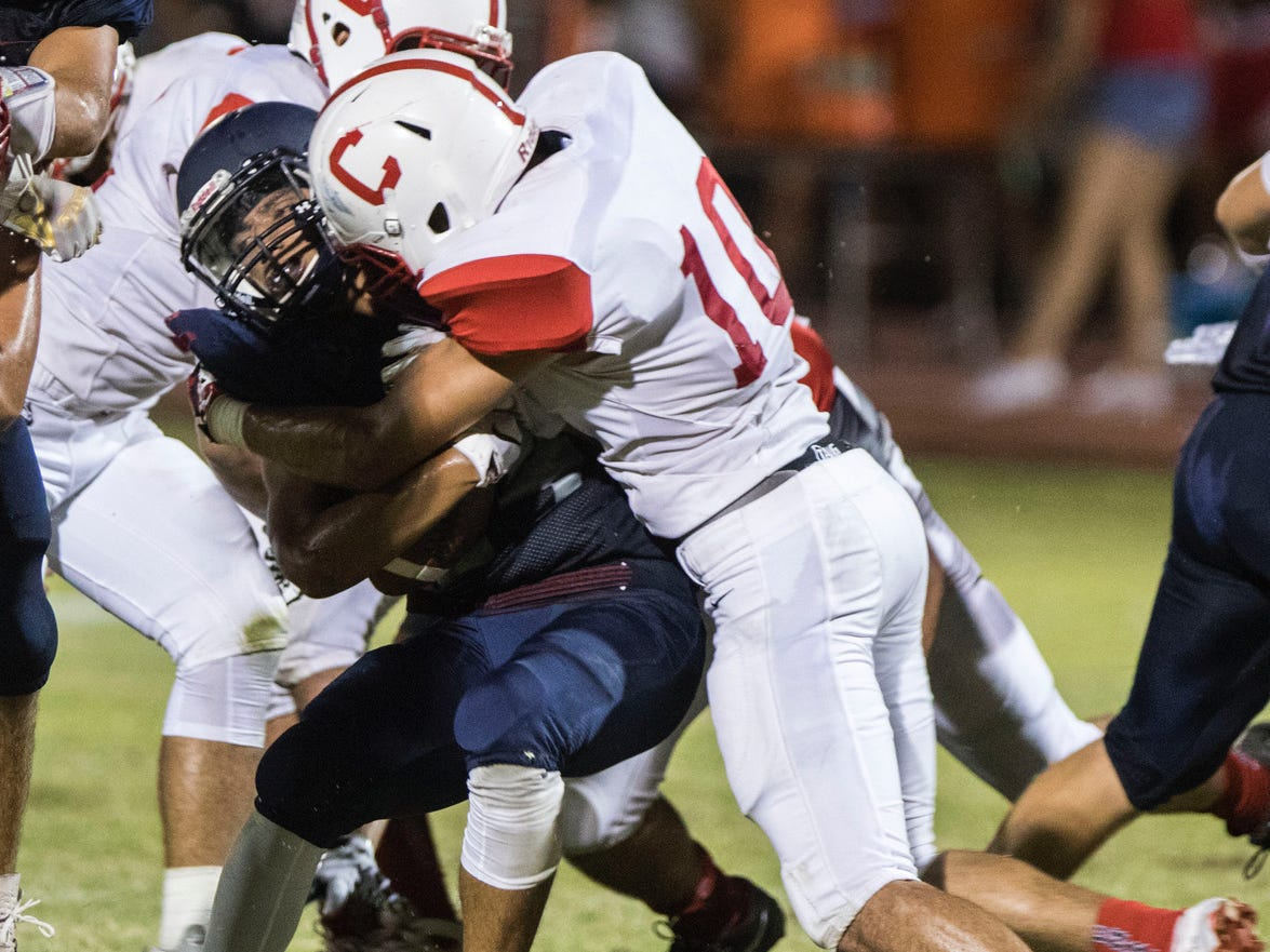 McClintock's Jt Trujillo gets crunched by Central's Mario Rodriguez during their game in Tempe Friday, Sept. 7, 2018. #azhsfb
