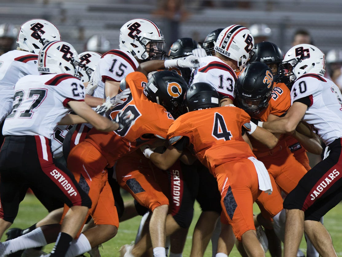 Boulder Creek's Hunter Burkett (13) gets manhandled by Corona Del Sol and his own teammates as they push him for extra yards during their game in Tempe Friday, Sept. 7, 2018. #azhsfb