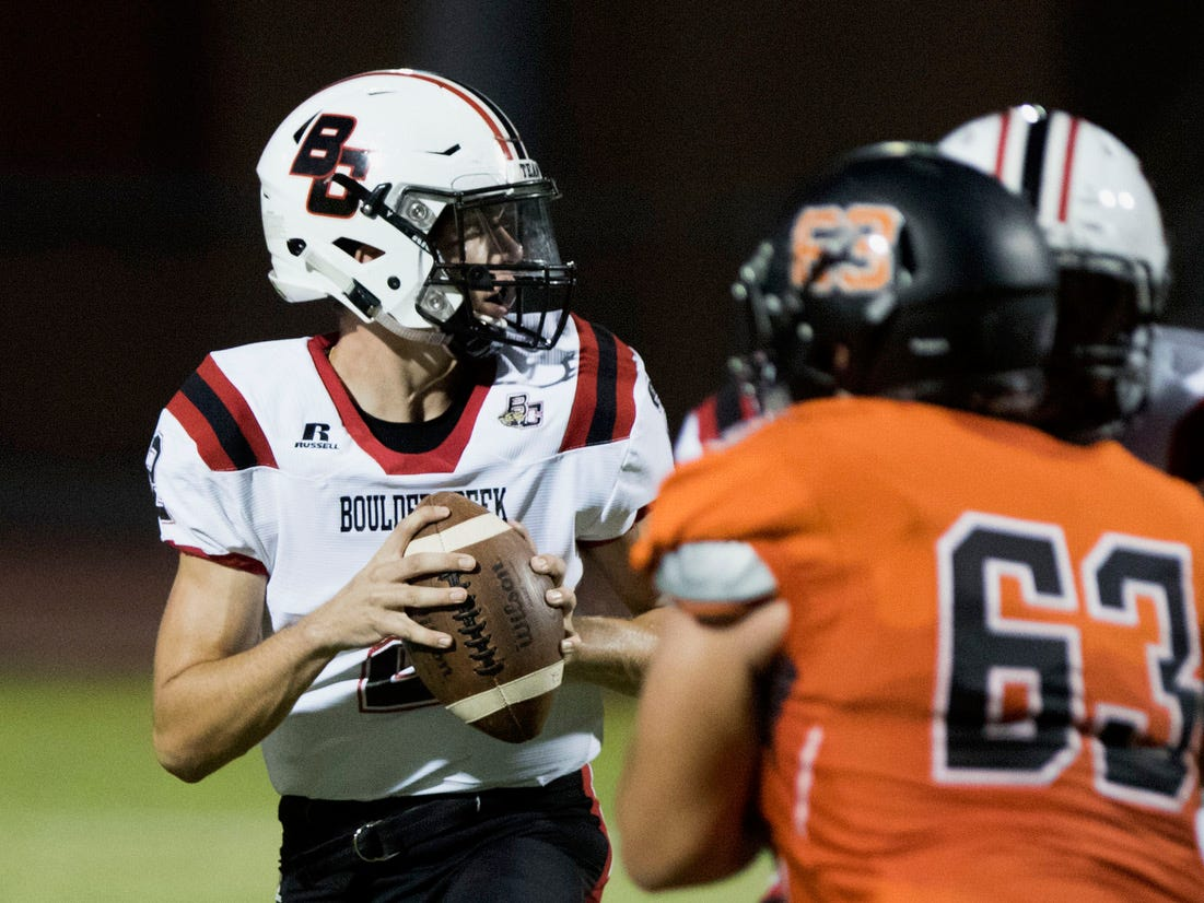 Boulder Creek quarterback Caden Austin looks for a receiver against the Corona Del Sol defense during their game in Tempe Friday, Sept. 7, 2018. #azhsfb