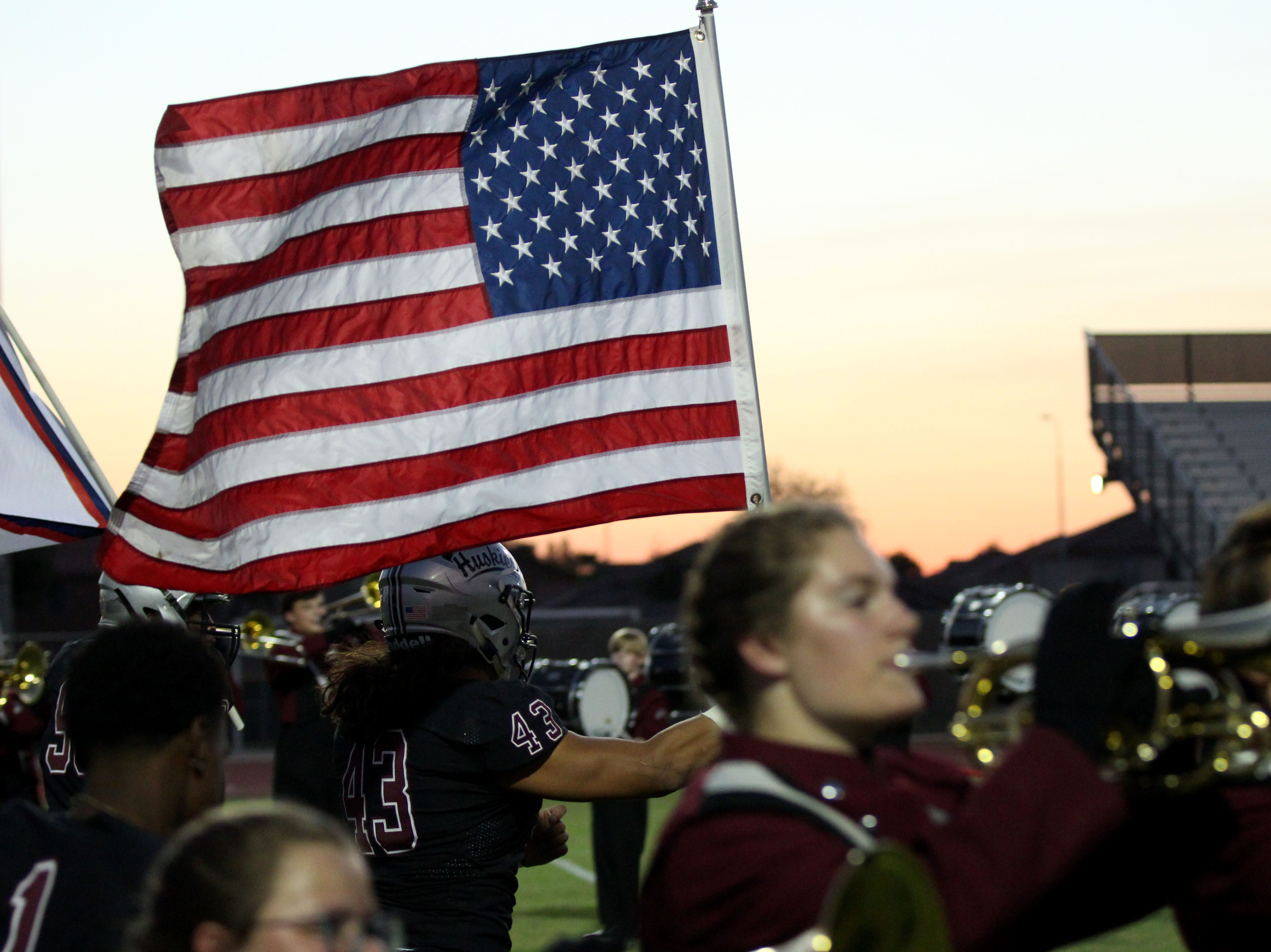 Hamilton takes the field with the United States flag before its game against Tolleson on Friday night in Chandler, Ariz. Sept. 7, 2018.
