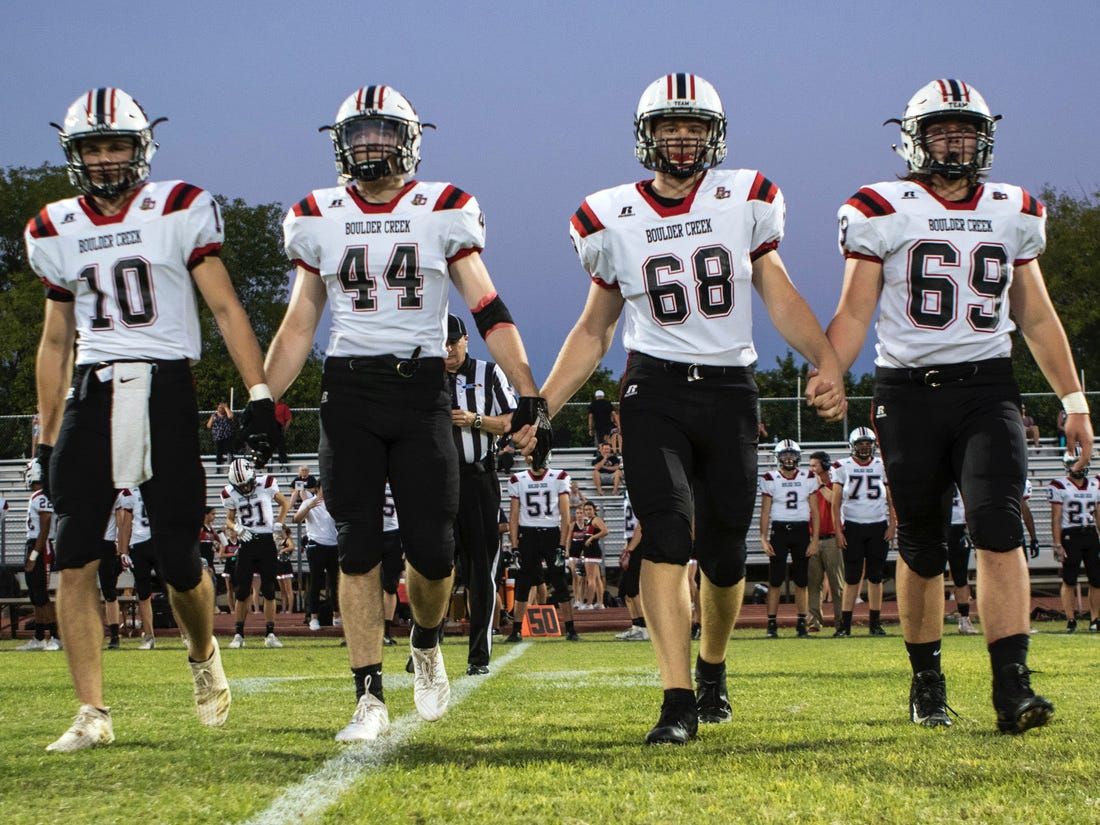 Boulder Creek captains Hendrix Johnson (10) Patrick Serrano(44) and Jonny Mooney (68) Myles Henderson (69) make their way to the middle of the field during their game with Corona Del Sol in Tempe Friday, Sept. 7, 2018. #azhsfb
