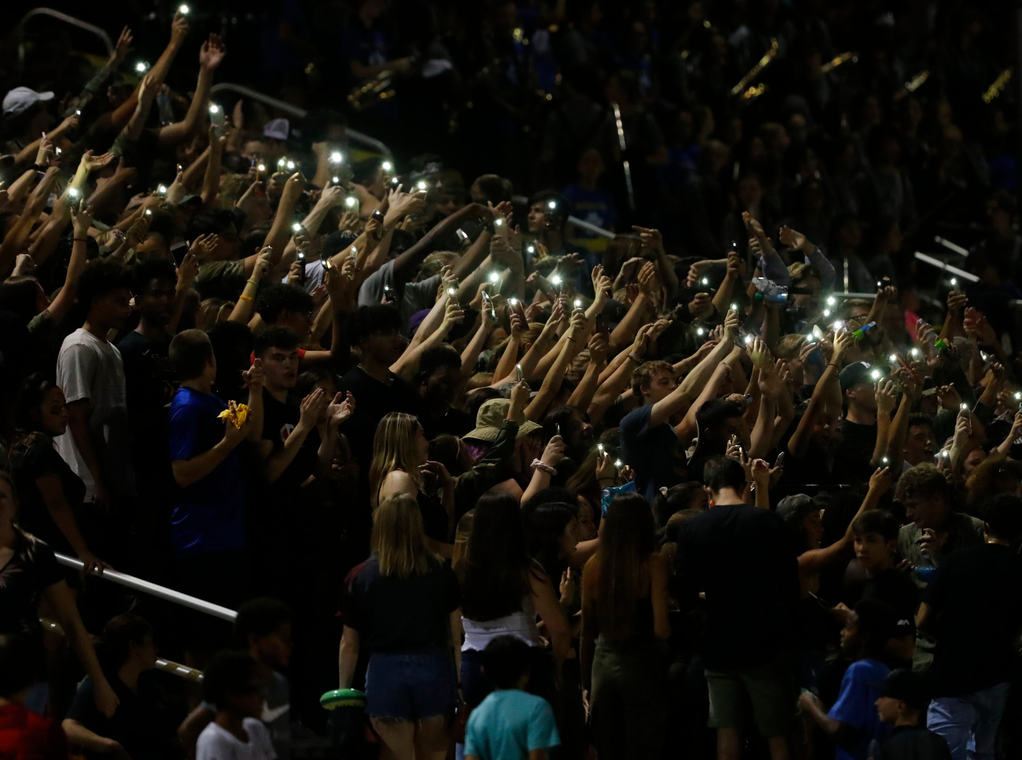 Millennium fans use their phones for lights as they chant during a game against Desert Edge at Millennium High School in Goodyear, Ariz. on Sept. 7, 2018.