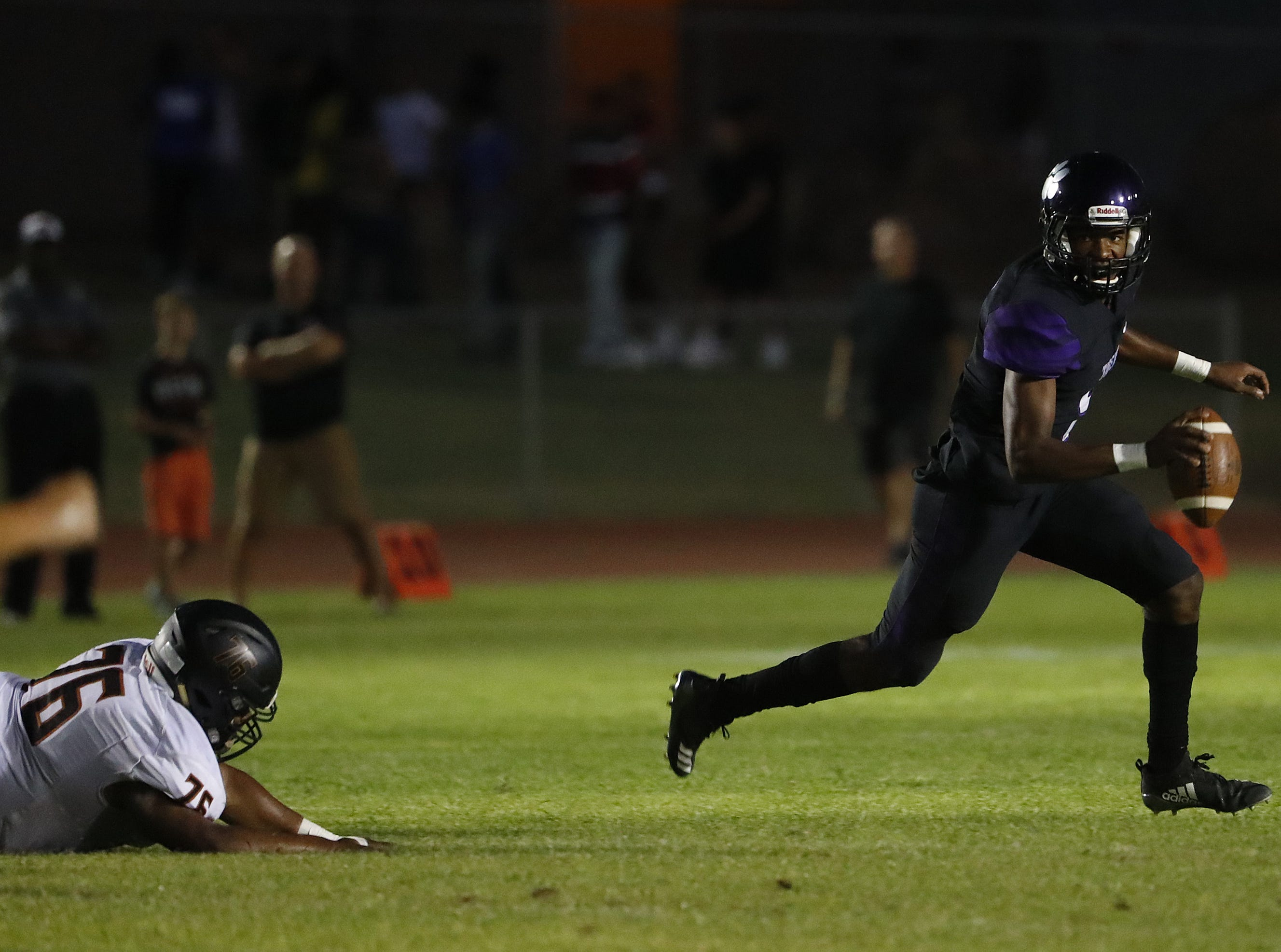 Millennium's Zareq Brown (5) scrambles away from Desert Millennium's Isaac Oliver (26) breaks a tackle from Desert Edge's Isaiah Williams (76) during a game at Millennium High School in Goodyear, Ariz. on Sept. 7, 2018.