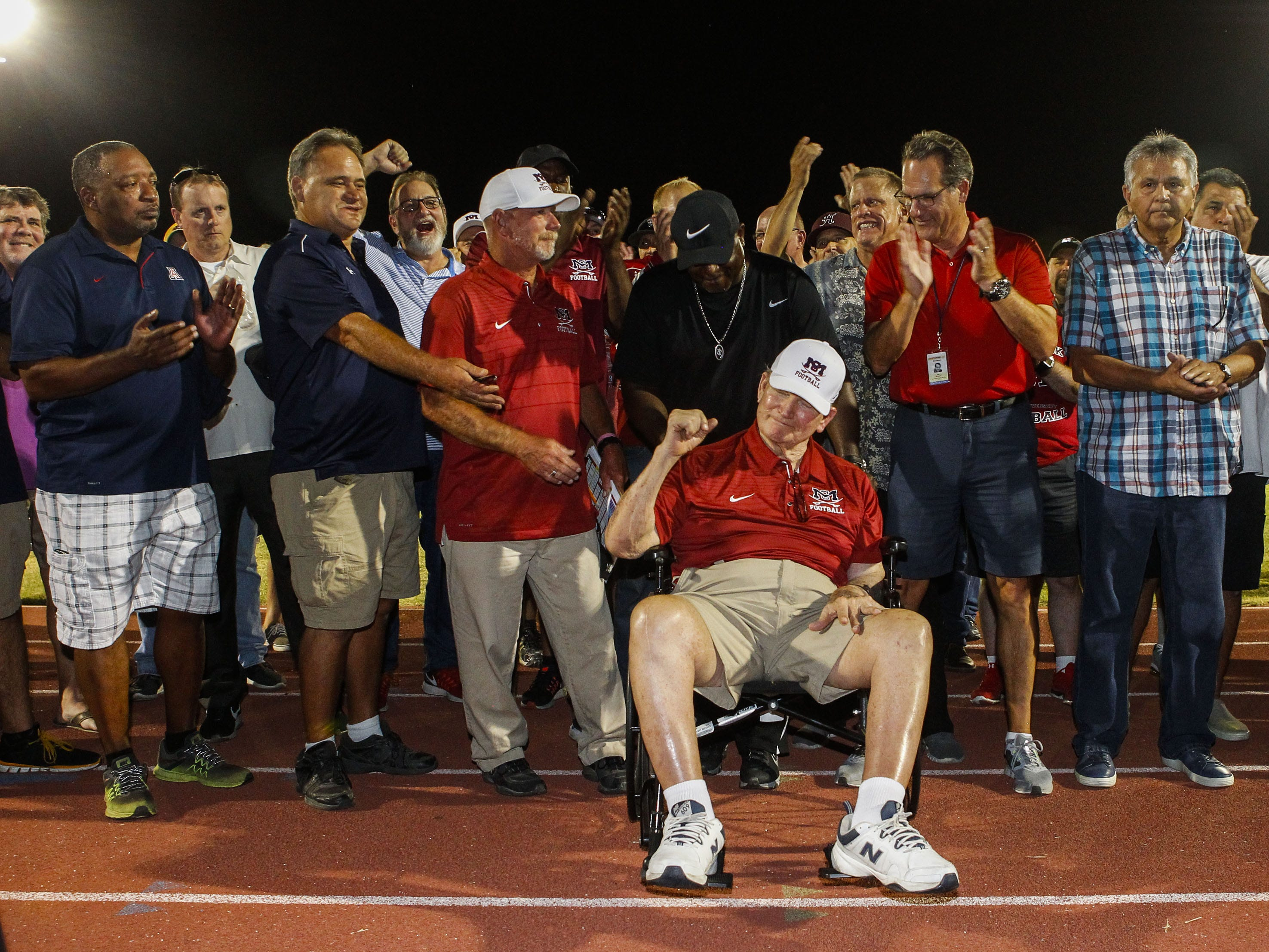 Surrounded by former student/athletes McClintock High School's original Head Coach Karl Kiefer is honored during halftime of the Chargers game with Central in Tempe Friday, Sept. 7, 2018. #azhsfb