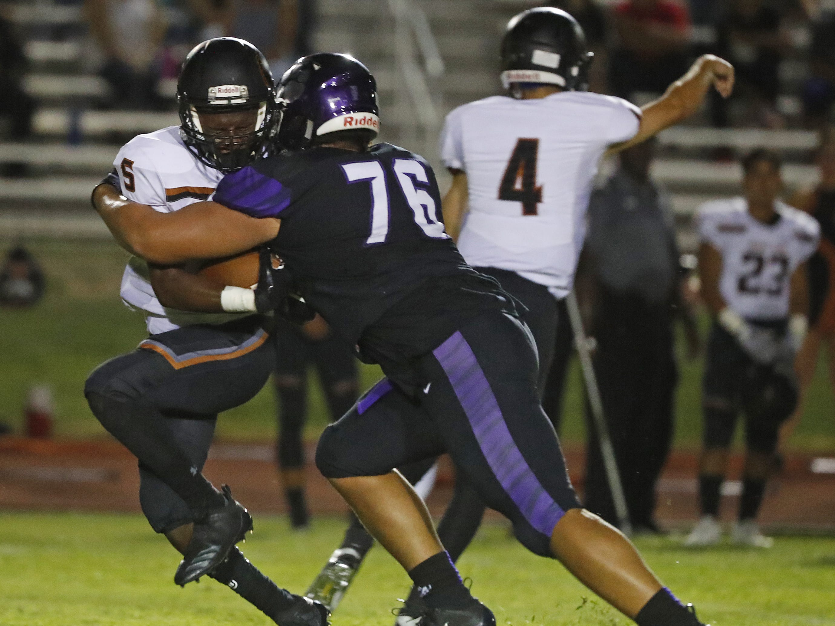 Millennium's Anthonie Cooper (76) tackles Desert Edge's Andrew Patterson (5) during a game at Millennium High School in Goodyear, Ariz. on Sept. 7, 2018.