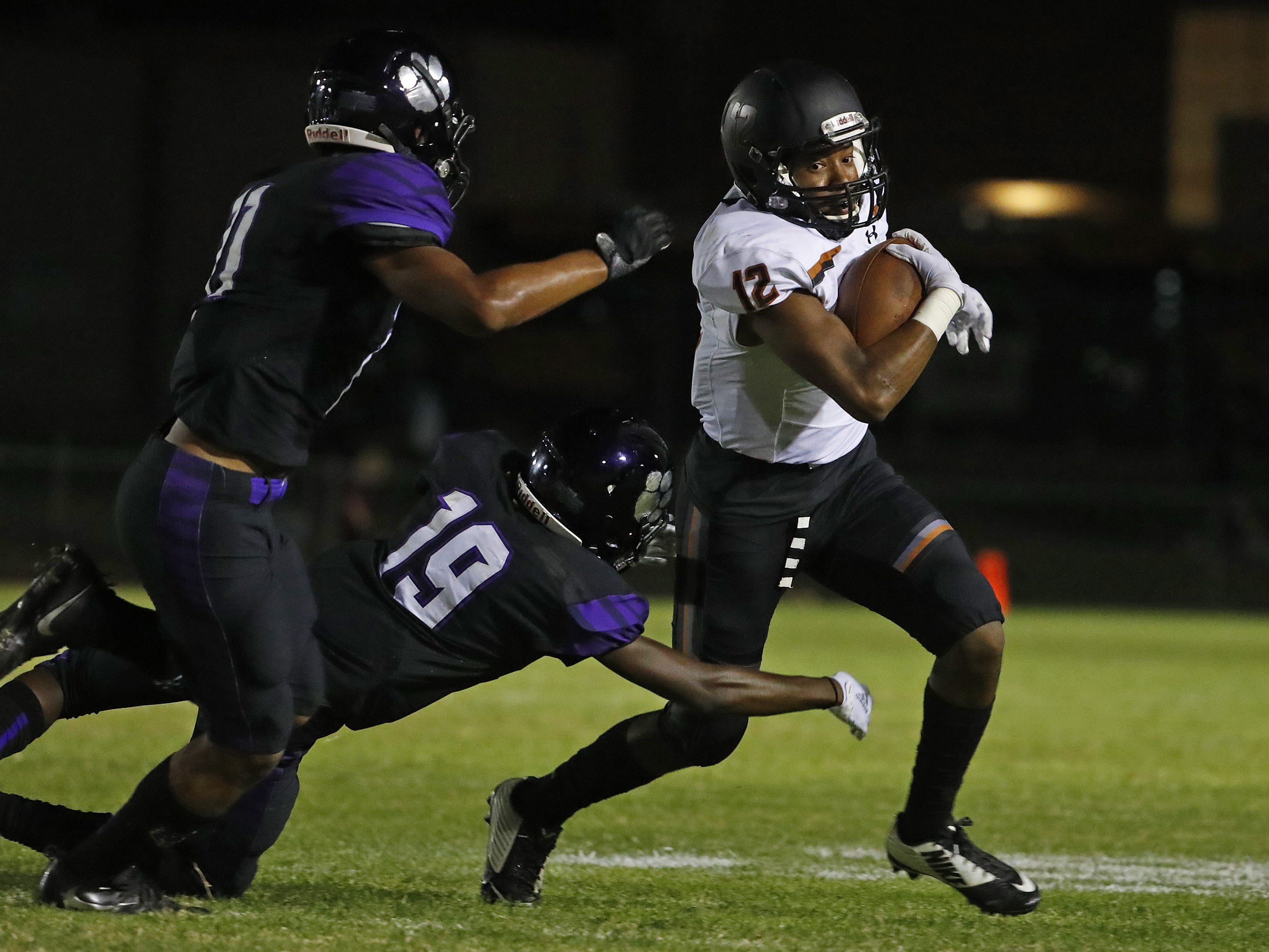 Desert Edge's Kennith Powell (12) breaks tackles from Millennium's Daylon Storey (11) and Kaysan Barnett (19) during a game at Millennium High School in Goodyear, Ariz. on Sept. 7, 2018.