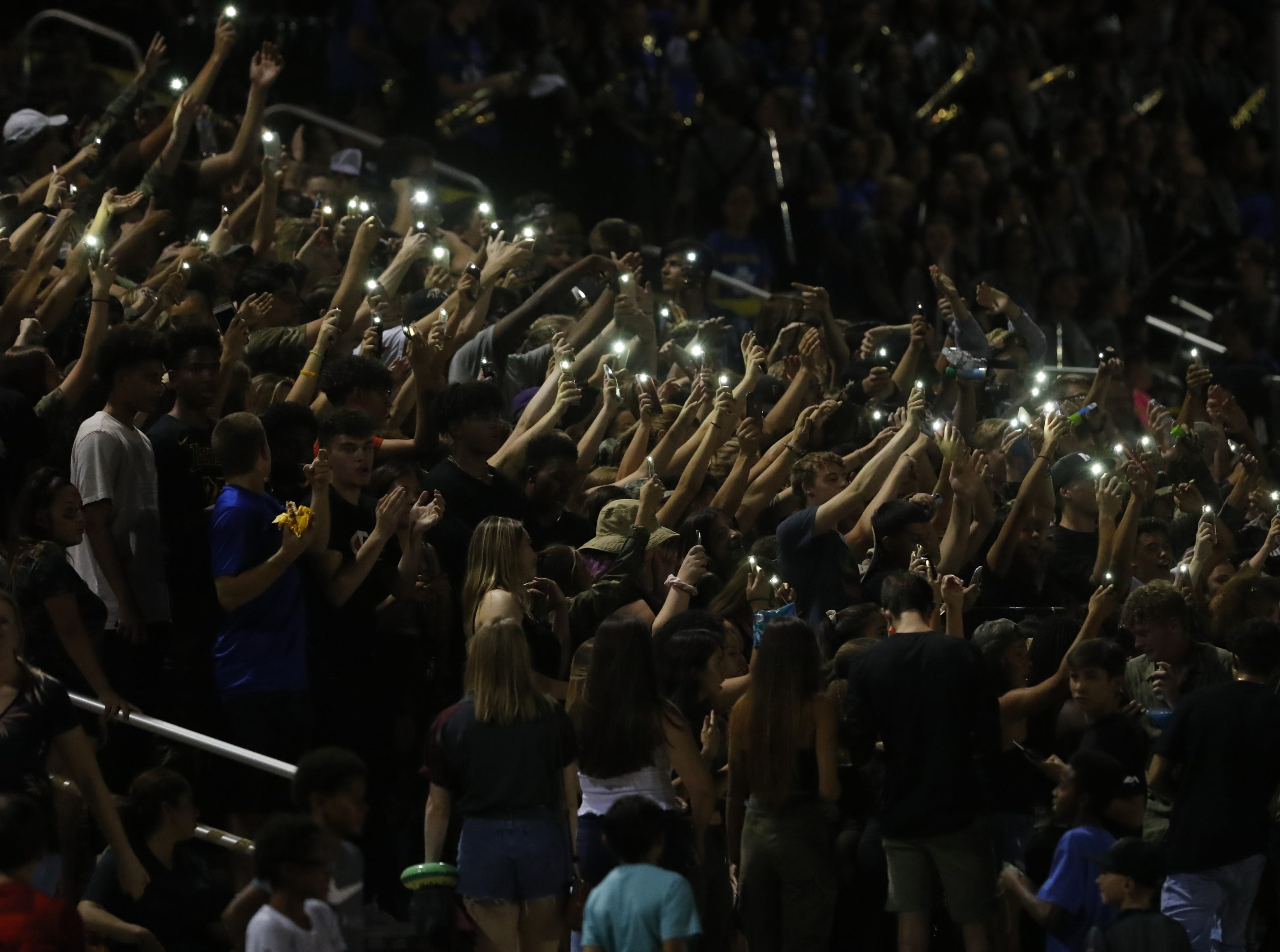 Millennium fans use their phones for lights as they chant during a game at Millennium High School in Goodyear, Ariz. on Sept. 7, 2018.