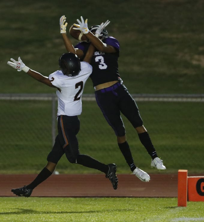 Millennium's Jaelon Taylor (3) and Desert Edge's Cliffonte McDowell fight for a pass in the end zone during a game at Millennium High School in Goodyear, Ariz. on Sept. 7, 2018.