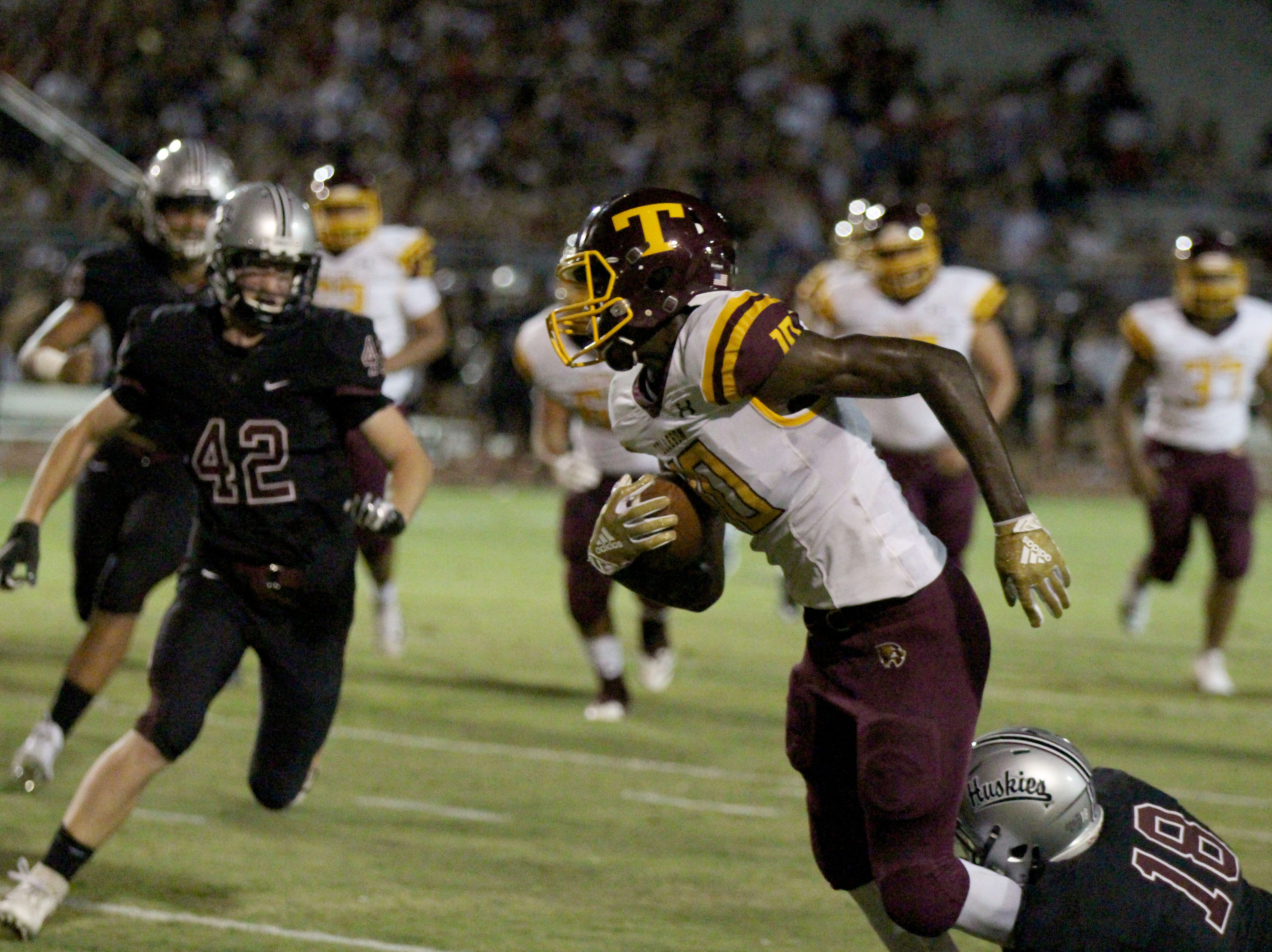 Tolleson's Andre Johnson (10) gets tackled by Hamilton's Jamar Brown (18) on Friday night in Chandler, Ariz. Sept. 7, 2018.