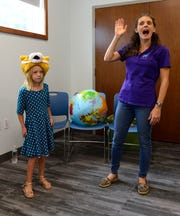 "Interactive storyteller Lindsay Bonilla  tells the fairytale ""The Bremen Town Musicians"" with the help of audience member Marian Sandvick, 7, at the Marblehead Peninsula Branch Library."